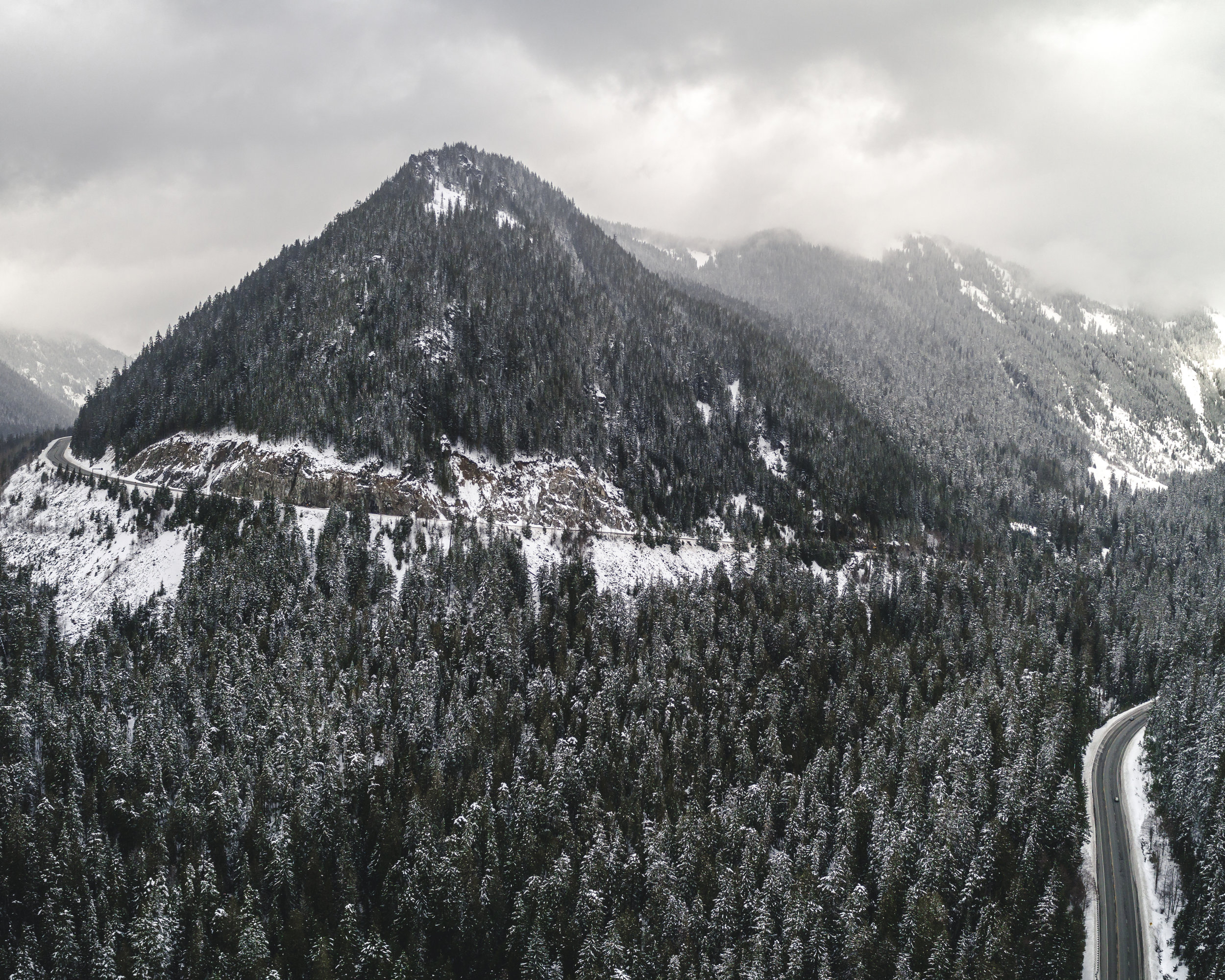 Dramatic_Snowy_Weather_Mountain_Highway_Aerial.jpg