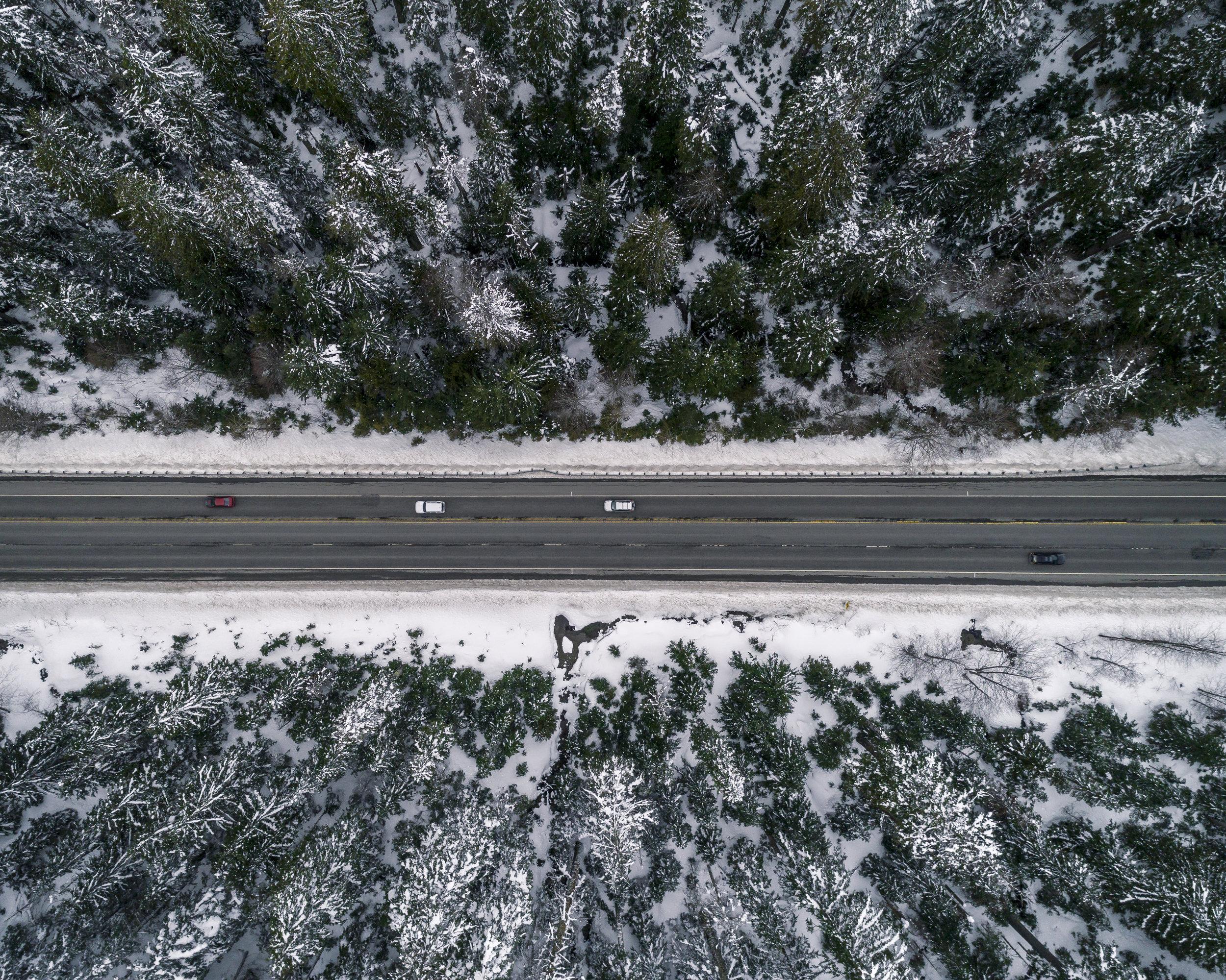 Birdseye_View_Snowy_Forest_Road_Travel_Aerial.jpg