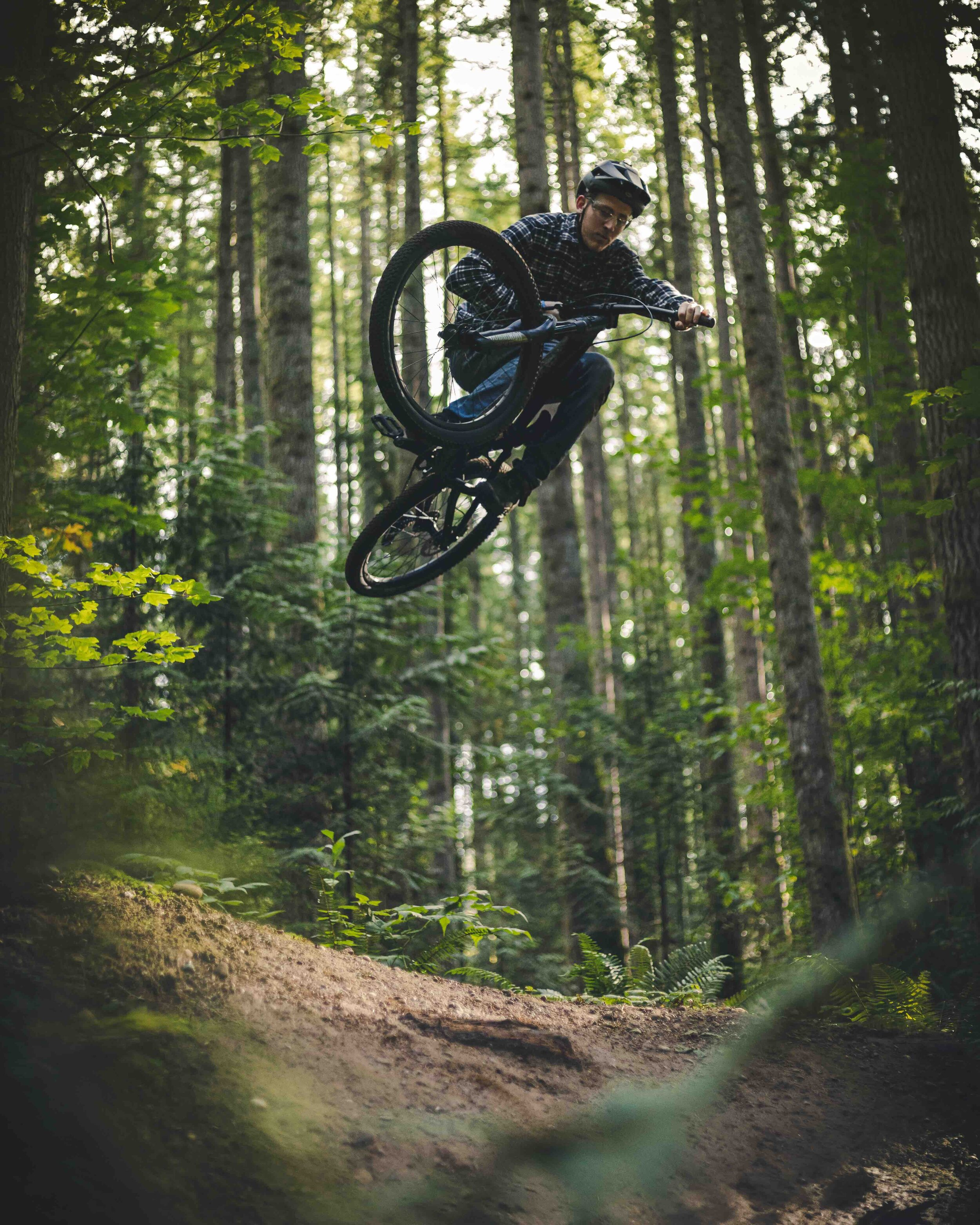 Artistic_Mountain_Bike_Jump_Air_Framed_by_Forest_Foliage.jpeg