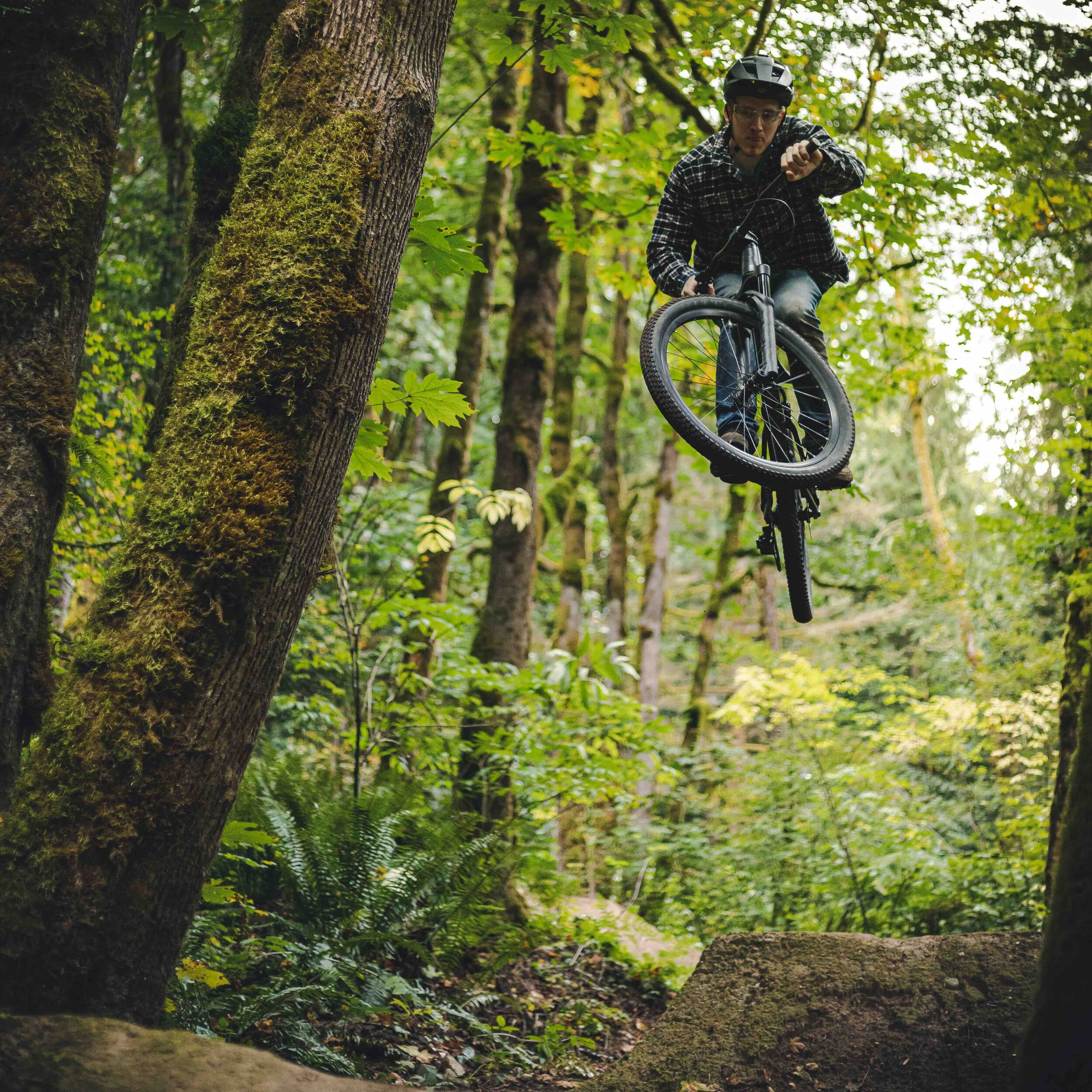 Man_Jumping_High_on_Dirt_Mountain_Bike_Jump_in_the_Woods.jpeg