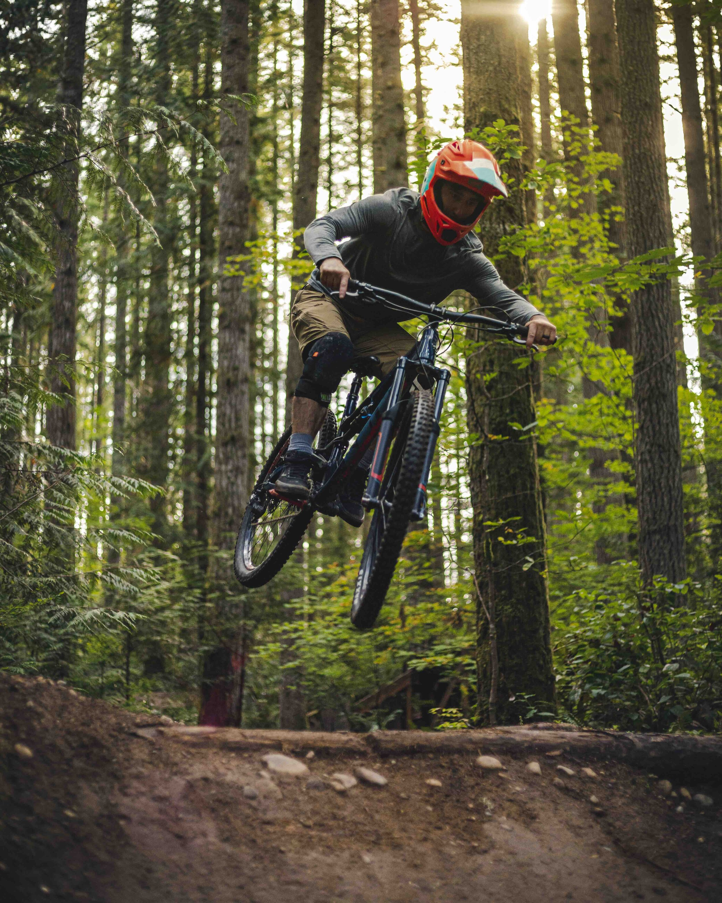 Mountain_Bike_Dirt_Jump_Action_Shot_Mid_Air_with_Forest_Background.jpeg