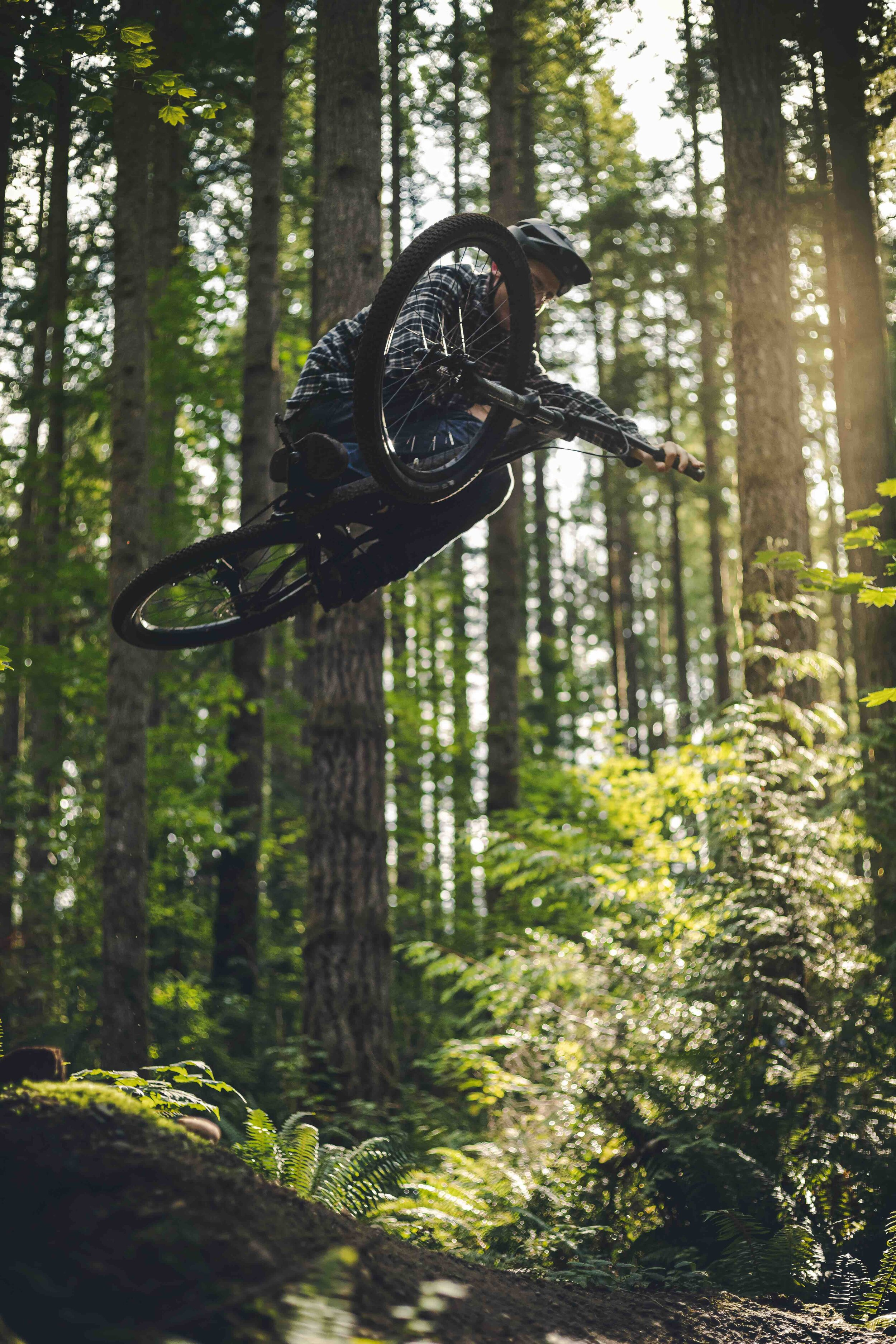 Stylish_Mountain_Bike_Air_with_Sideways_Trick_Over_Forest_Trees.jpeg