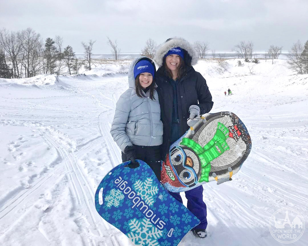 Where to go sledding in Muskegon, Michigan? Sugar Bowl Dune in Muskegon State Park! Near Muskegon Winter Sports Complex. An exciting winter activity in West Michigan. #sledding #openwidetheworld