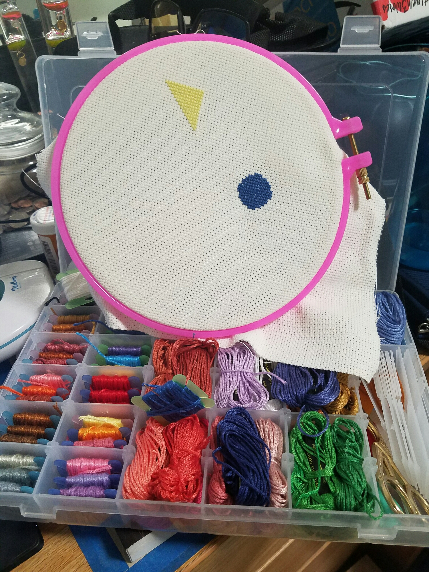 Photo: A cross-stitch on a hoop depicting a yellow triangle and a blue circle, resting on a box of embroidery supplies.