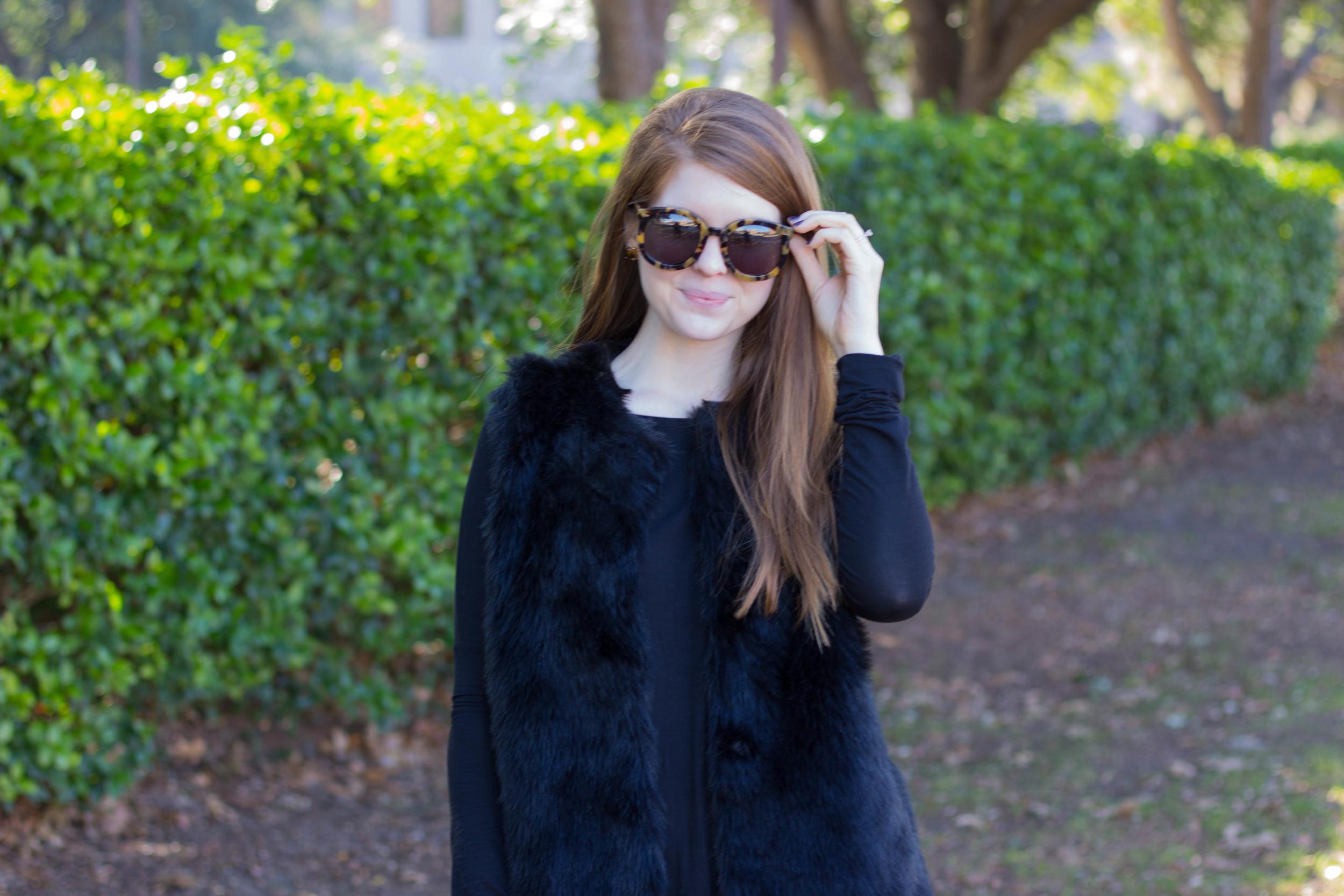 black fur vest, black piko tunic, karen walker tortoise sunglasses, j crew tuxedo pant, black crowd booties