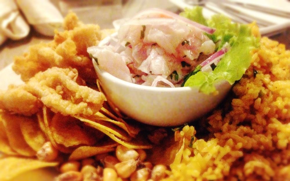 A bowl of ceviche with salsa criolla, chicharron de pescado, chifles and canchas.
