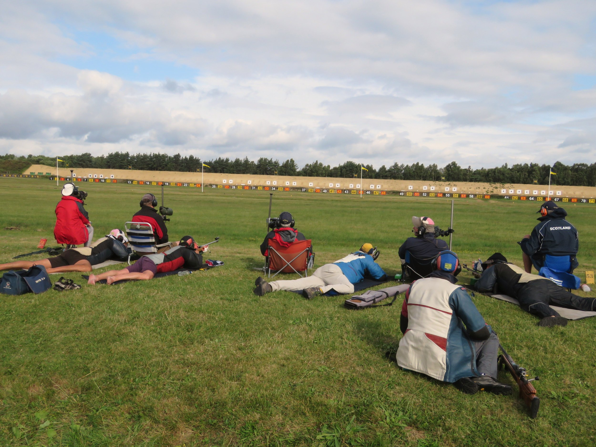 GB team in Kolapore match in typical two target format: Main Wind coach central, plotters on extreme left and right and target coaches sitting between two firers.  Sandy Walker left hand firer on left target, Ian Shaw (lightblue jacket) and Bruce Logan right, plotting for right hand target.