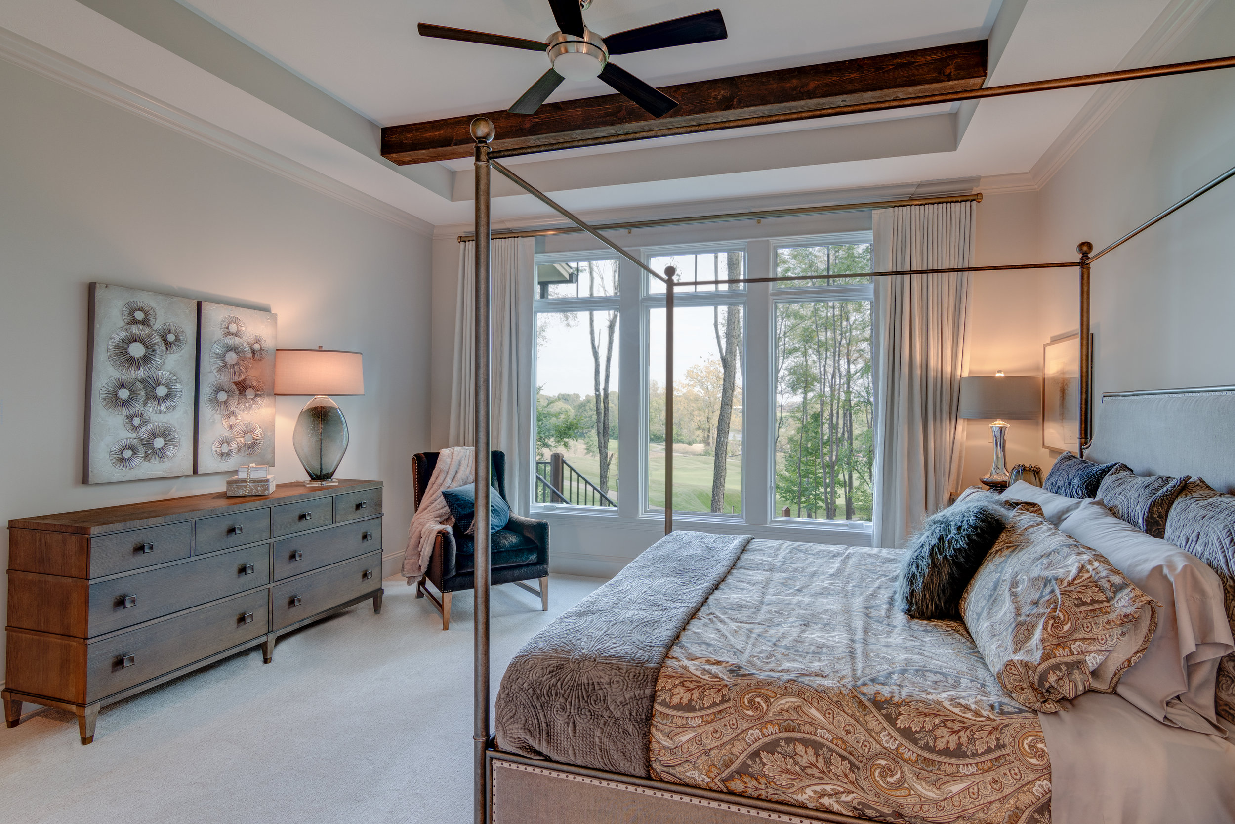 Large windows bring in the maximum natural light in this master bedroom.