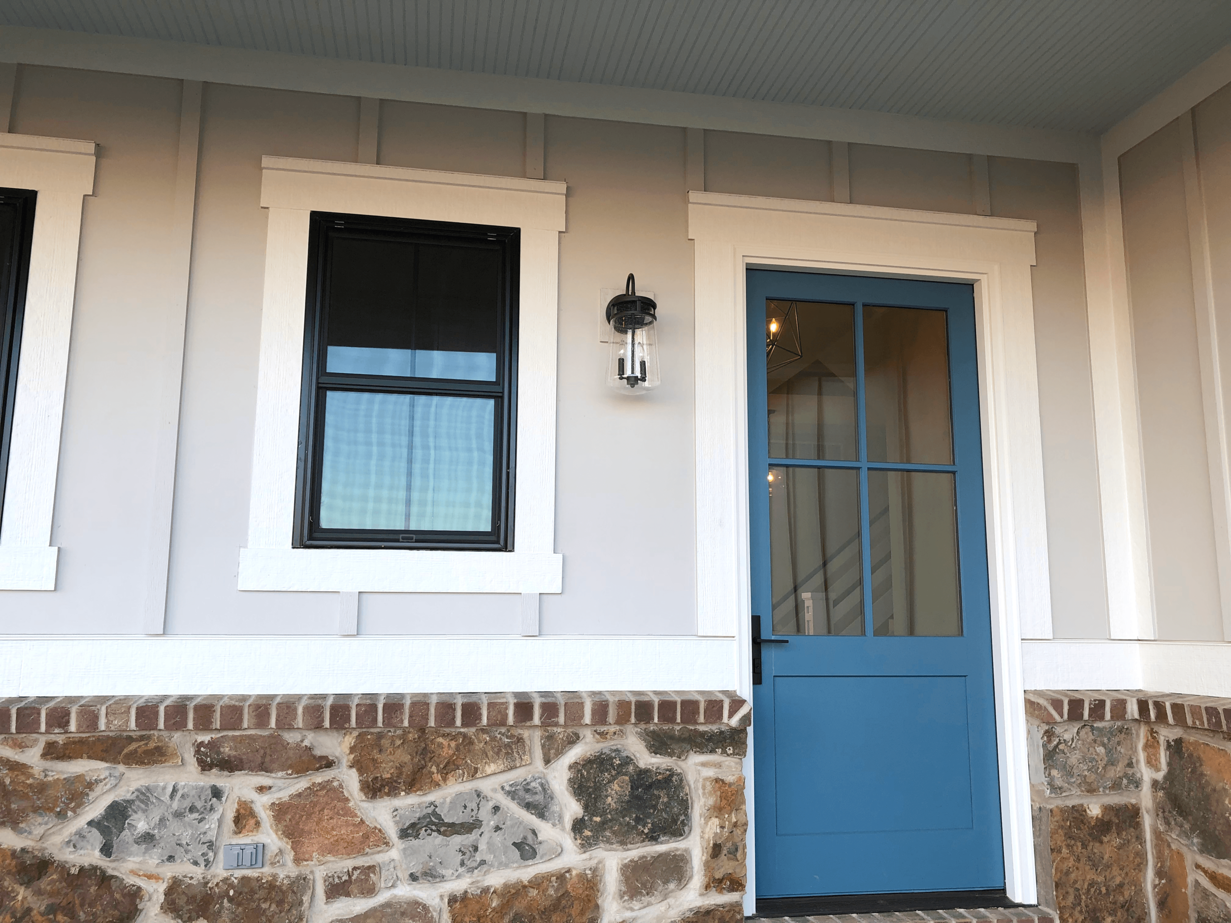 This vibrant blue door stands out against the cream and white siding.