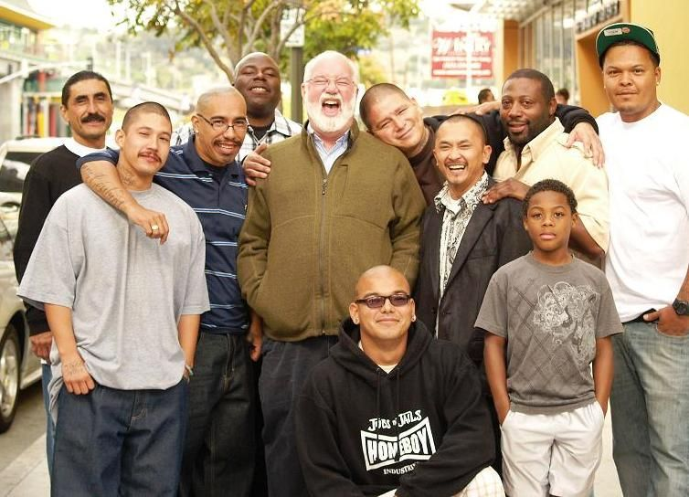 Fr. Gregory Boyle, S.J. poses with young members of Homeboy Industries in Los Angeles, CA.