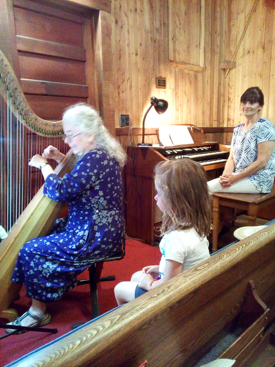This little girl loves Mary Muckle's harp at Good Samaritan