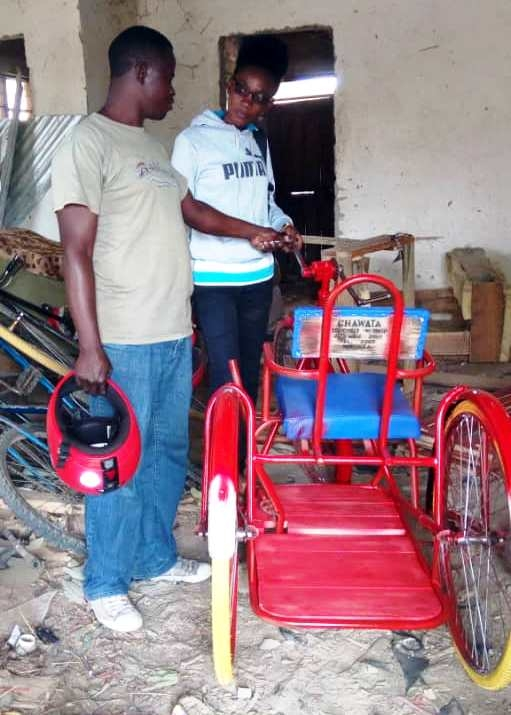 Field Officer Jackie inspecting the progress of  the tricycle at the repair shop
