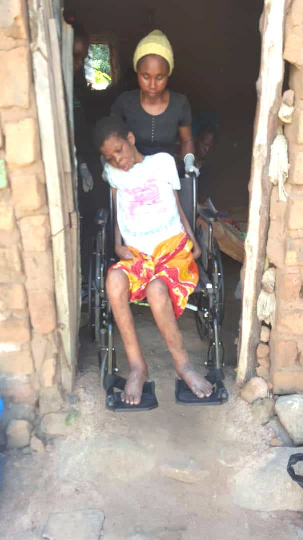 Neema, CBR's medical technician, wheeling Peruzi out in her brand new wheelchair to feel the sunshine.