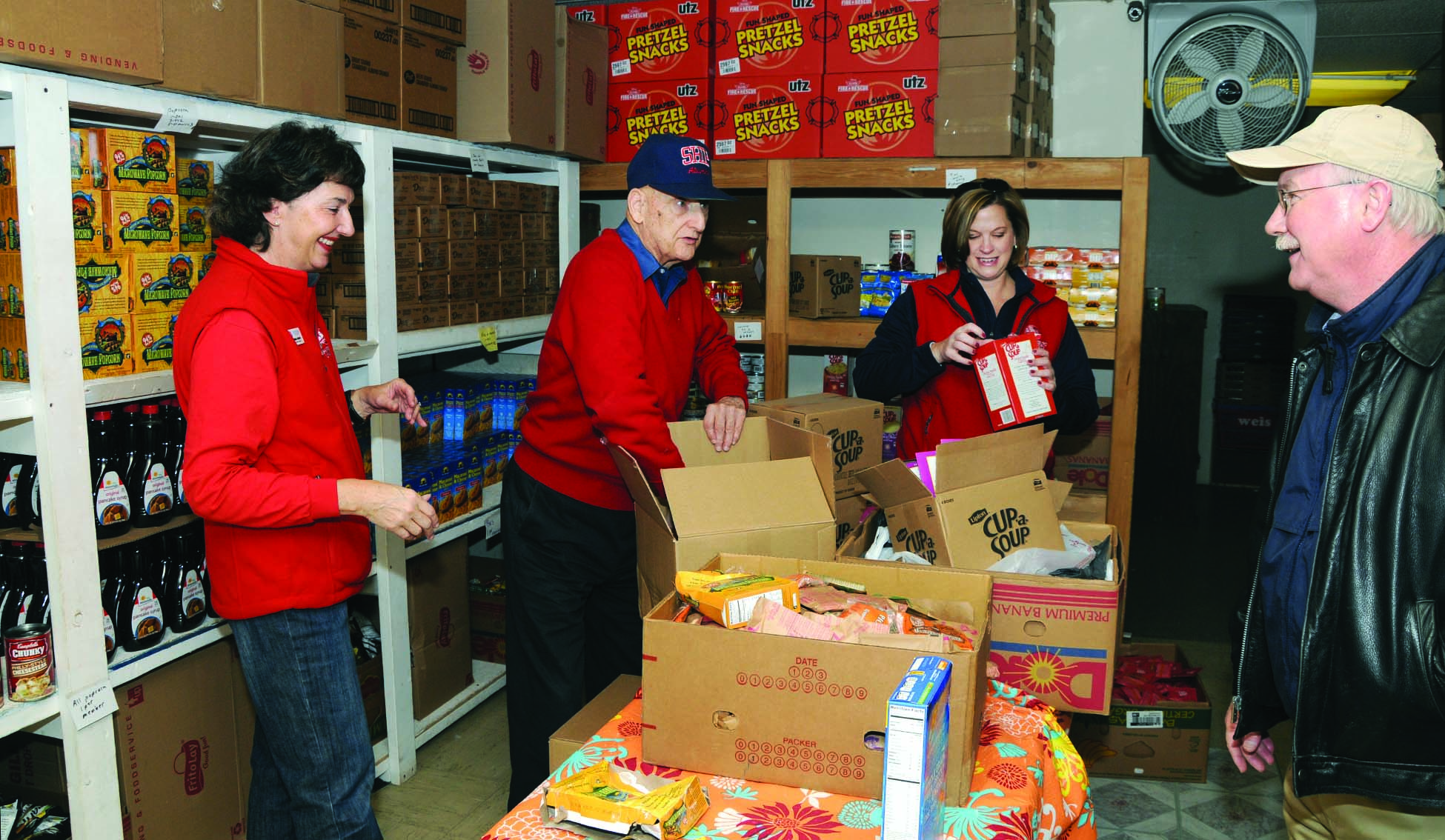 Dr. Jody Harpster, president (right) and Ship alumni (from left) Brenda Gabler '77–'80M, Ray Reber '55, and Lorie Davis '98M restock shelves at King's Kettle Food Pantry as part of Homecoming weekend.