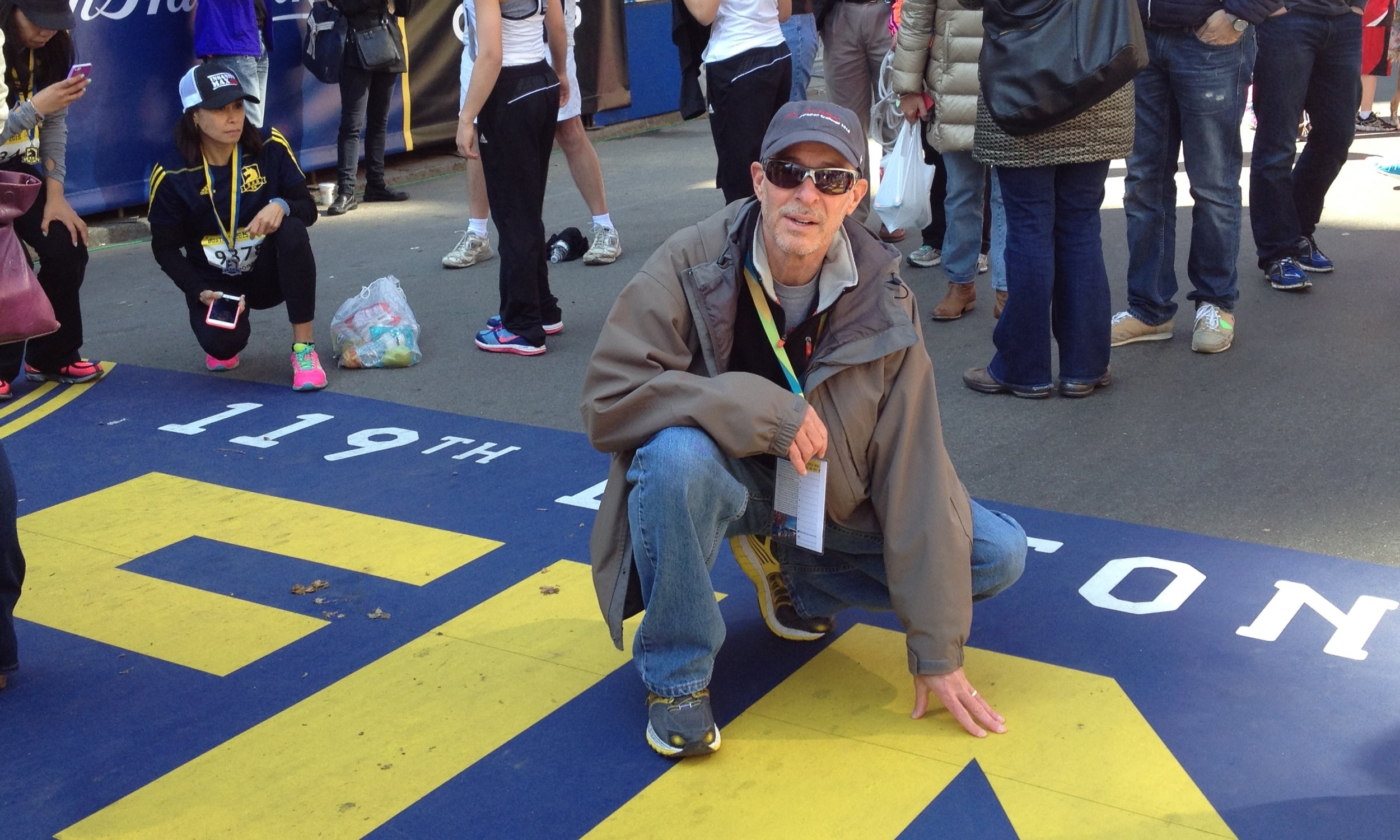 Taking a moment at the finish line, (above) Ken Shur '75-'82M remembers the victims of the Boston Bombing and the reason he runs the marathon.