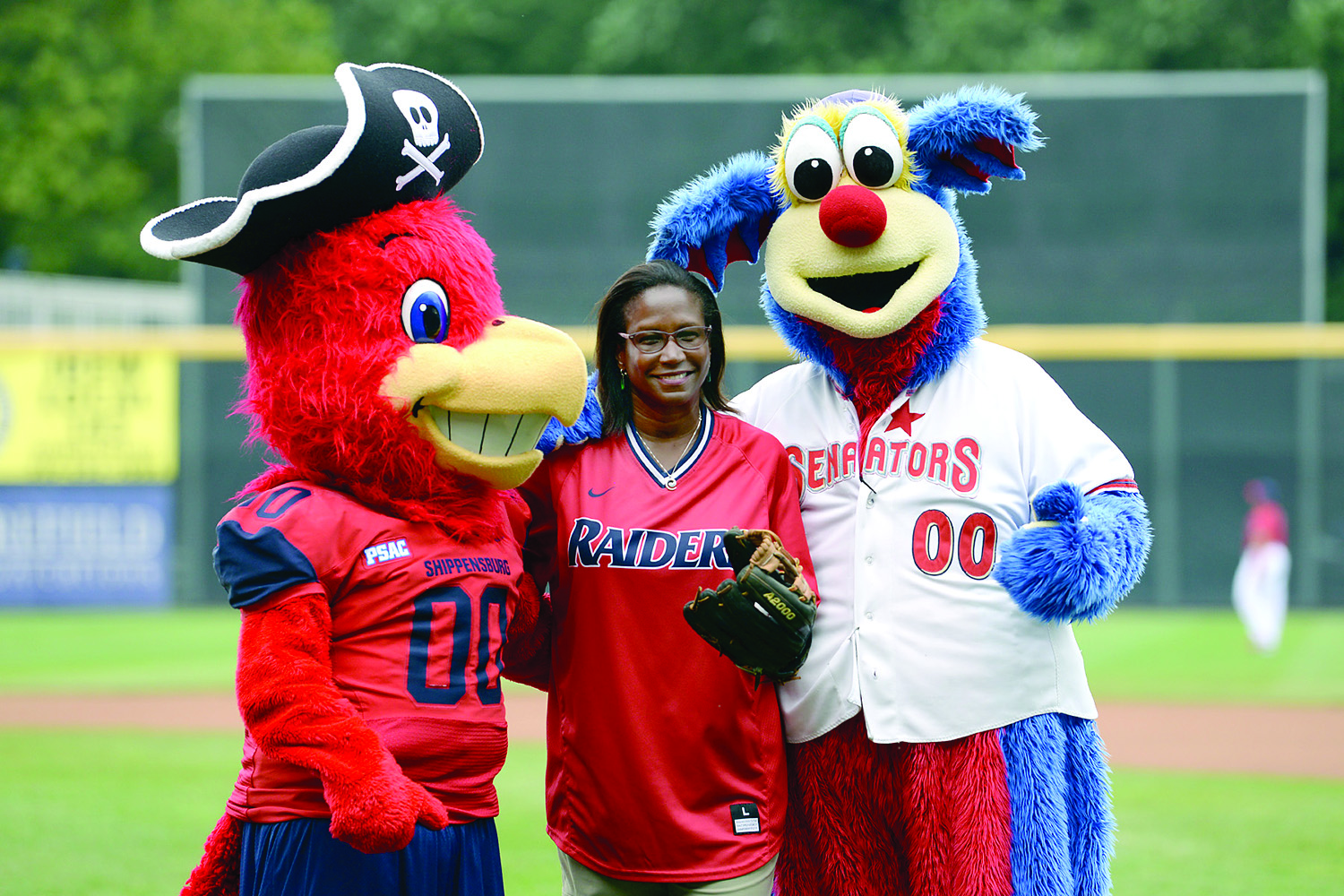 President Laurie Carter takes time for a photo with Big Red and the Harrisburg Senators' Rascal during Ship Night with the Senators in August.