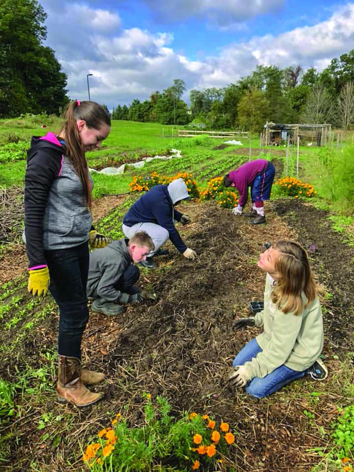 Teen Leadership students help to weed beds and plant kale at the SU Farm.