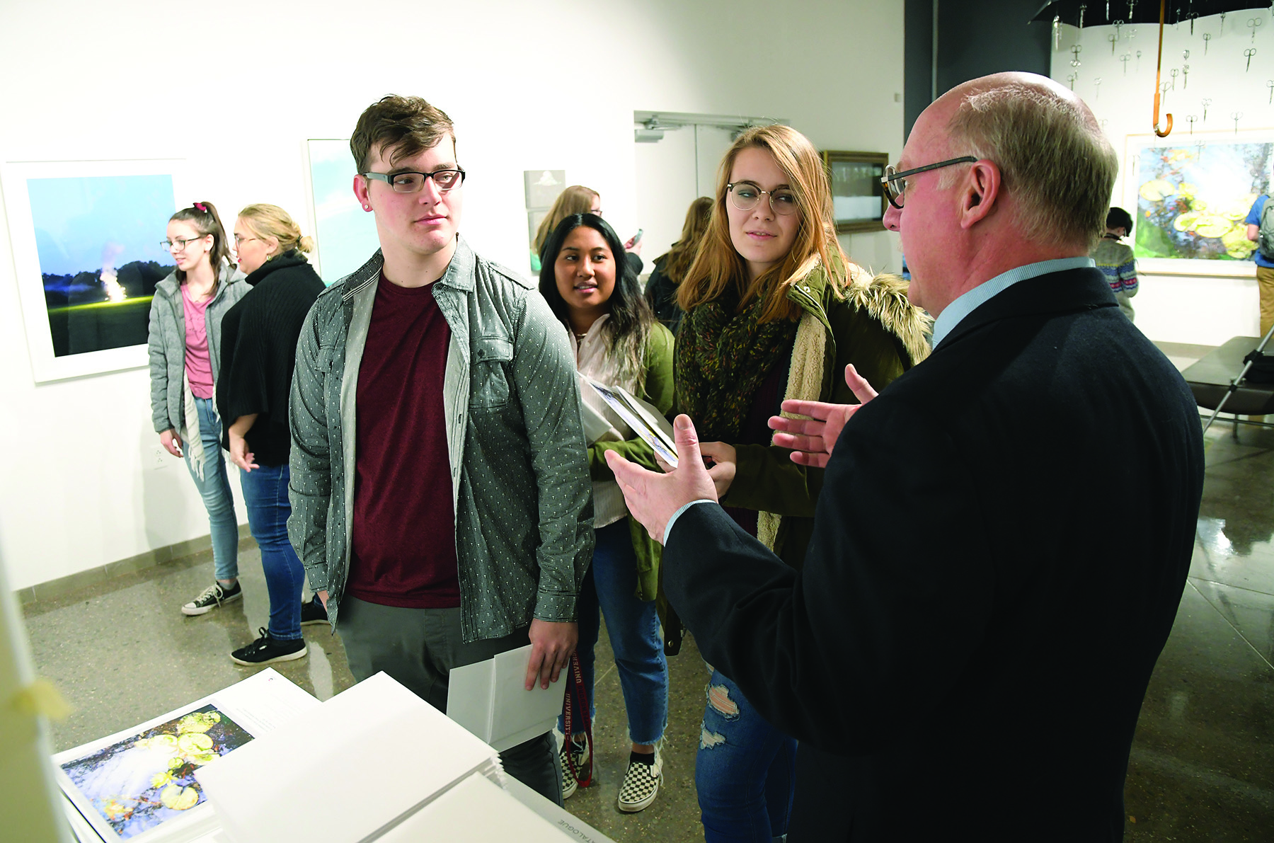 Professor Michael Campbell (right) talks with art and design students at the exhibit opening.
