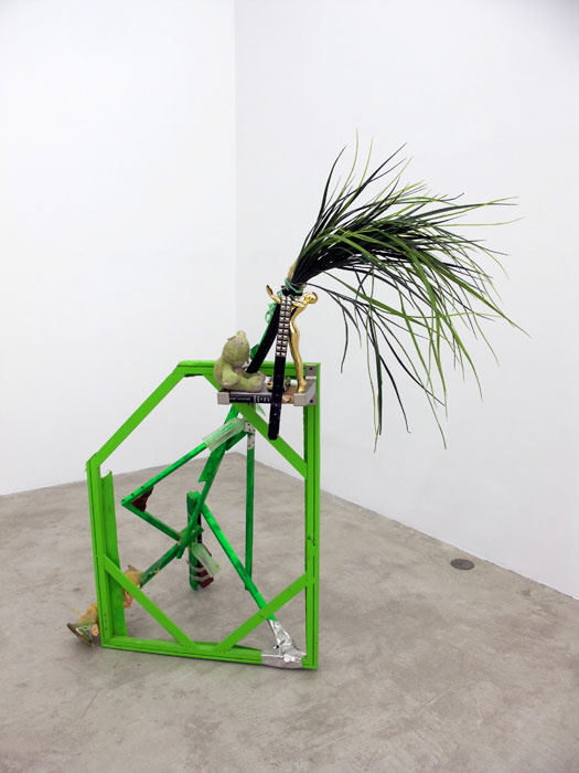 Justin Lieberman,  The Green Party Monument with Bookshelf , 2011, wood, aluminum, studded belt, brass candle stick, resin, brick, pipe, frog, car, brass statue, champagne flutes, 65 x 54 x 32 in