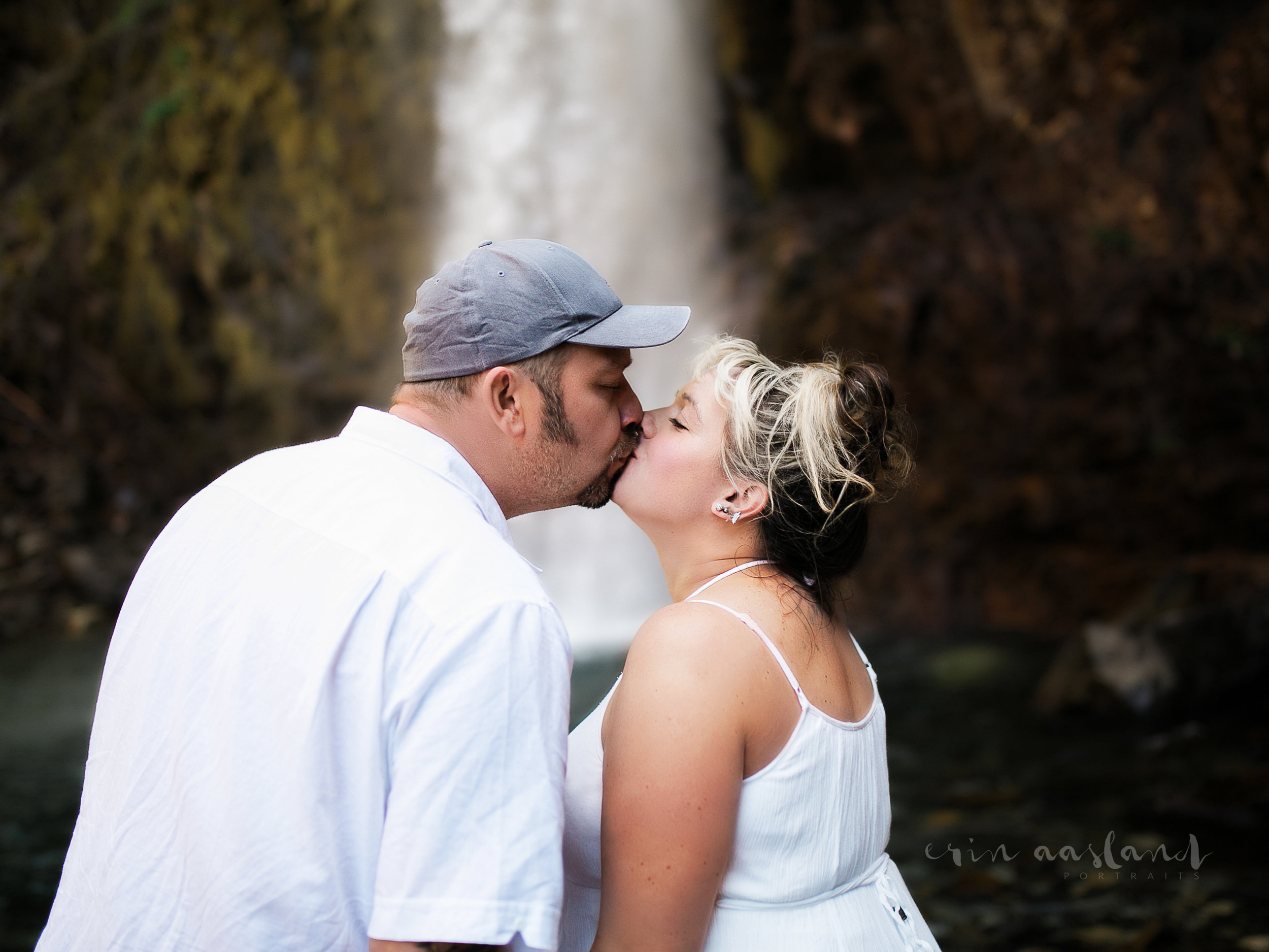 Maternity session couple kissing by waterfall