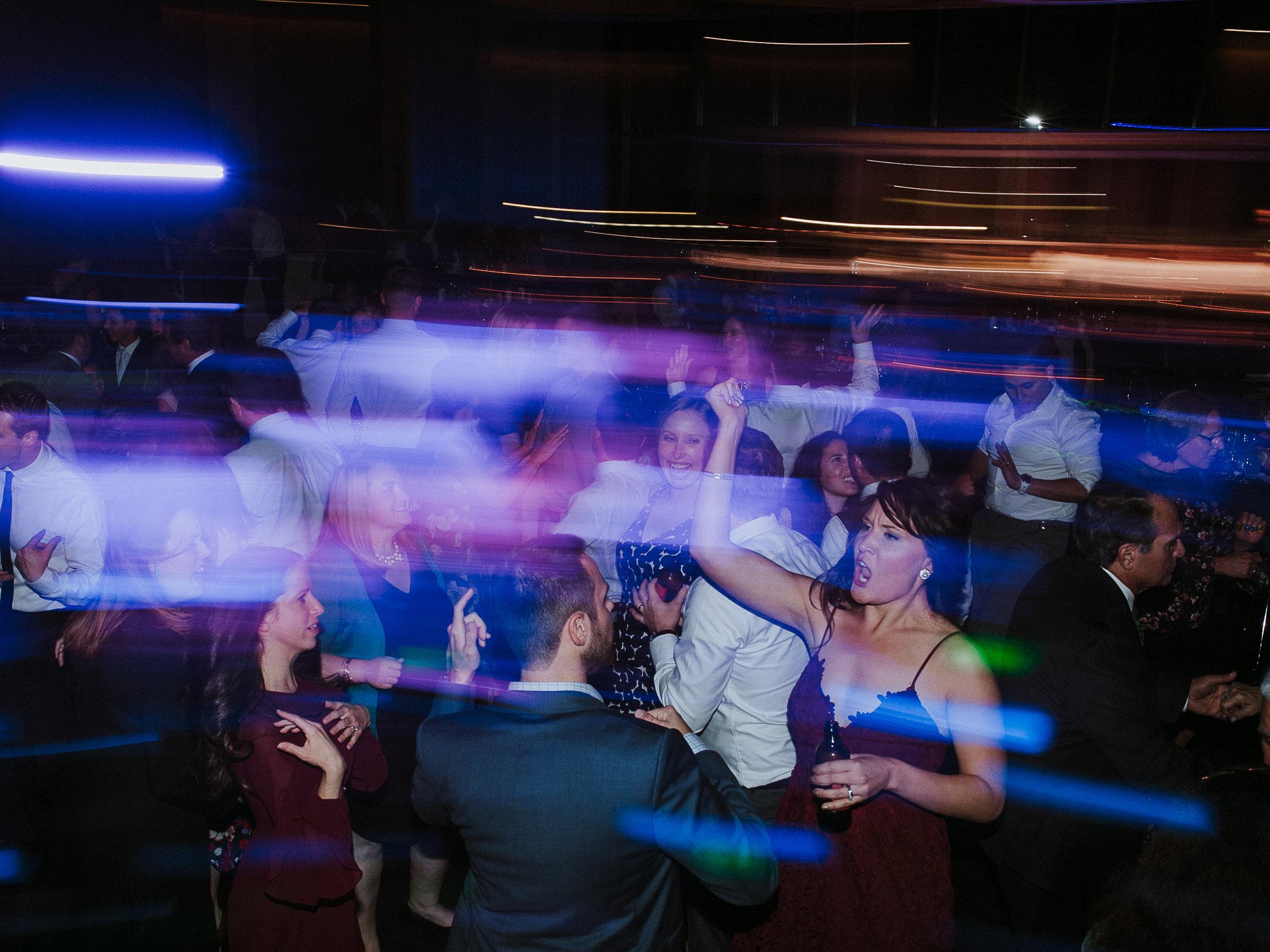 guests dancing at reception light blur
