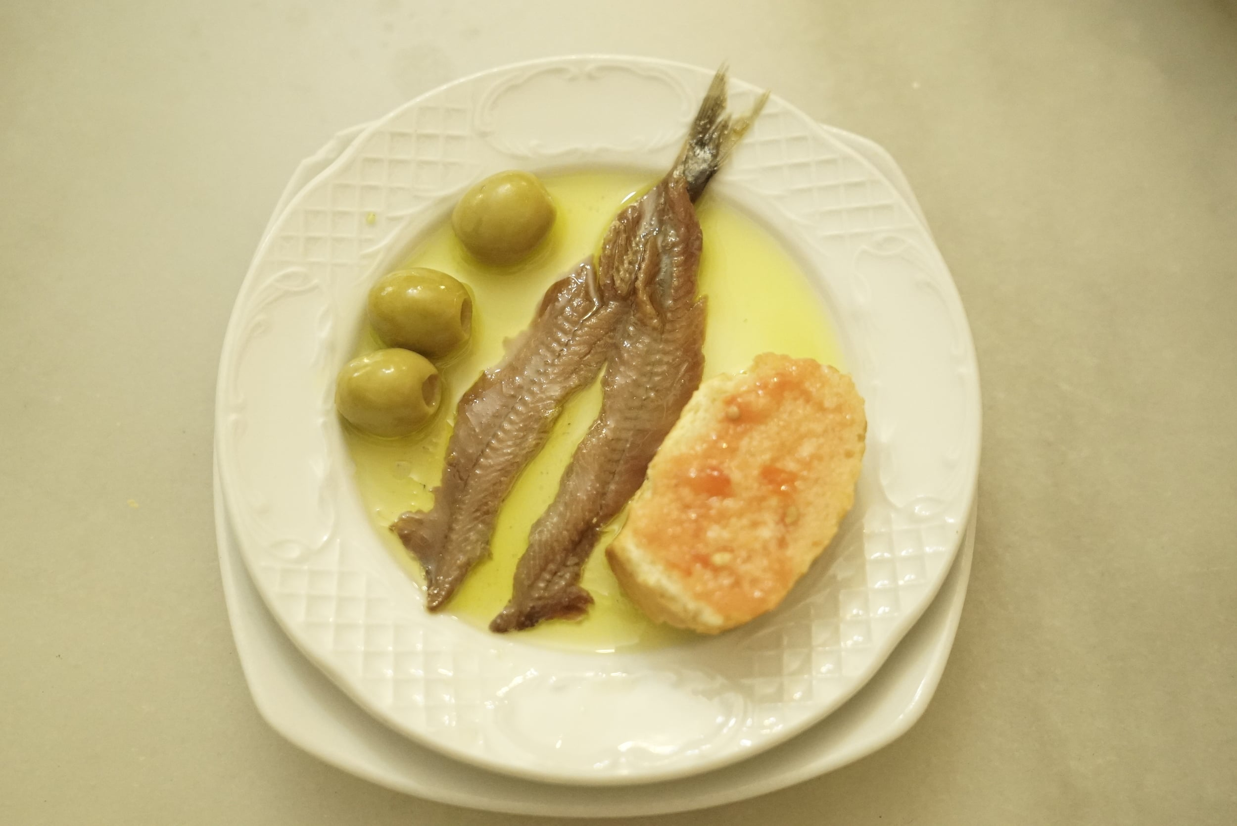 Anchovies olives and bread on a white plate.jpg