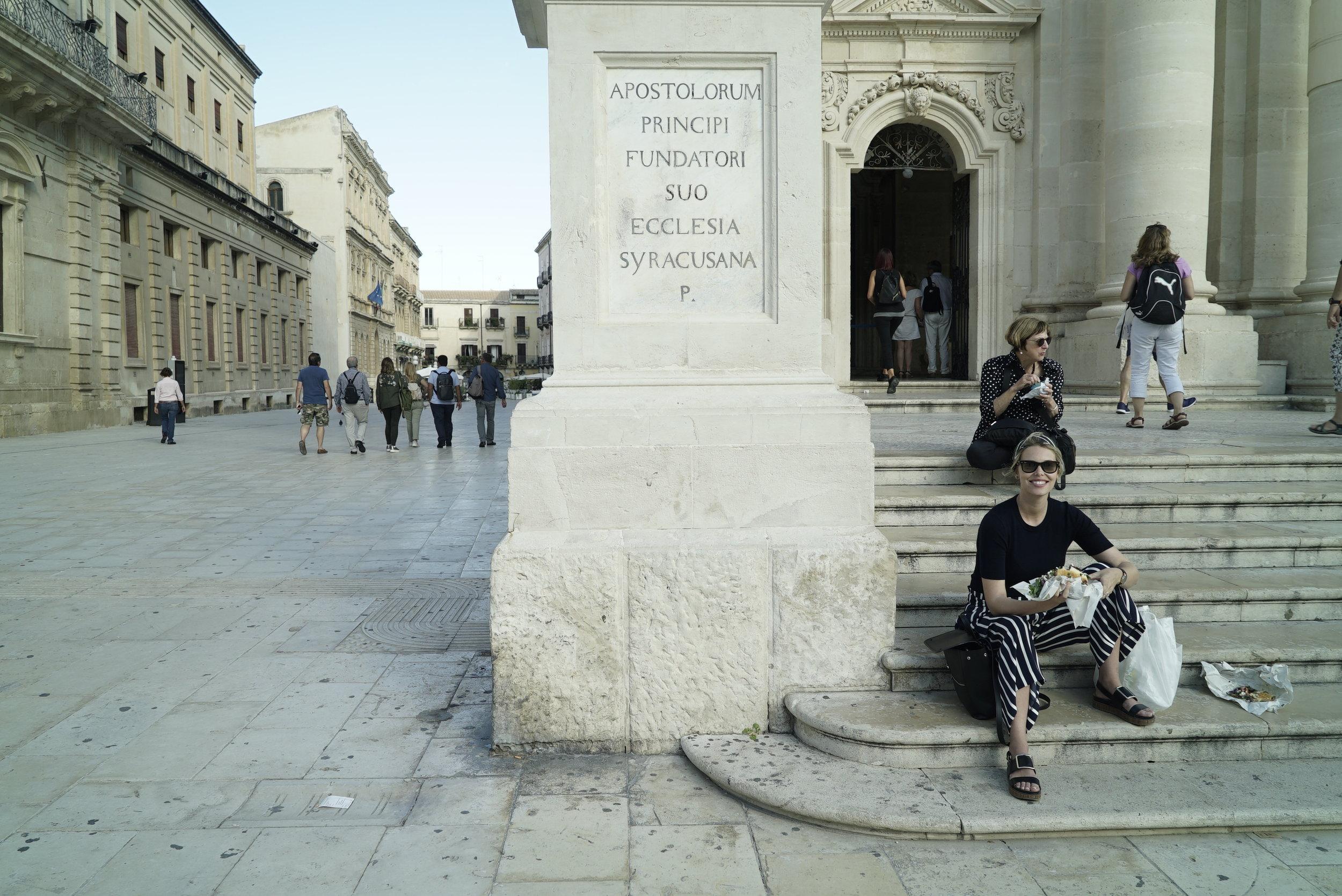eating panini on the steps of ortigia duomo.JPG