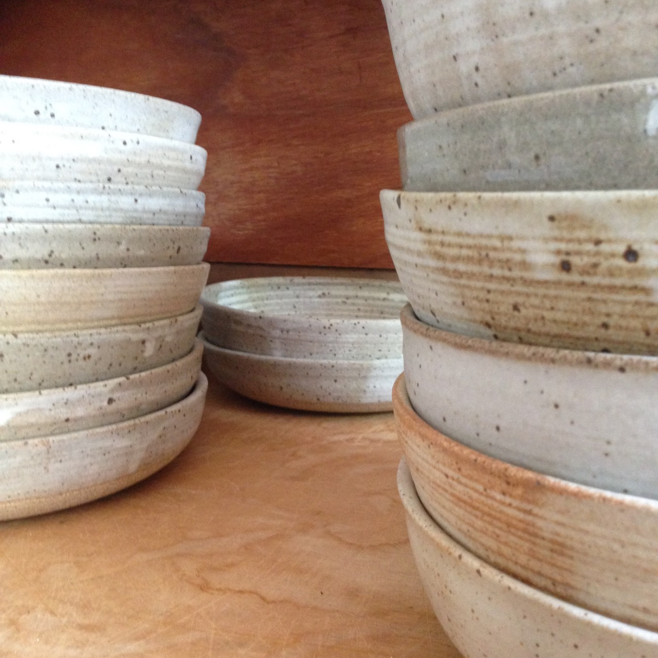 I make stacks of hand-thrown dinner bowls that are the same size. I can make them in matching glazes, but I also like to create sets with subtly varying tones, like these.