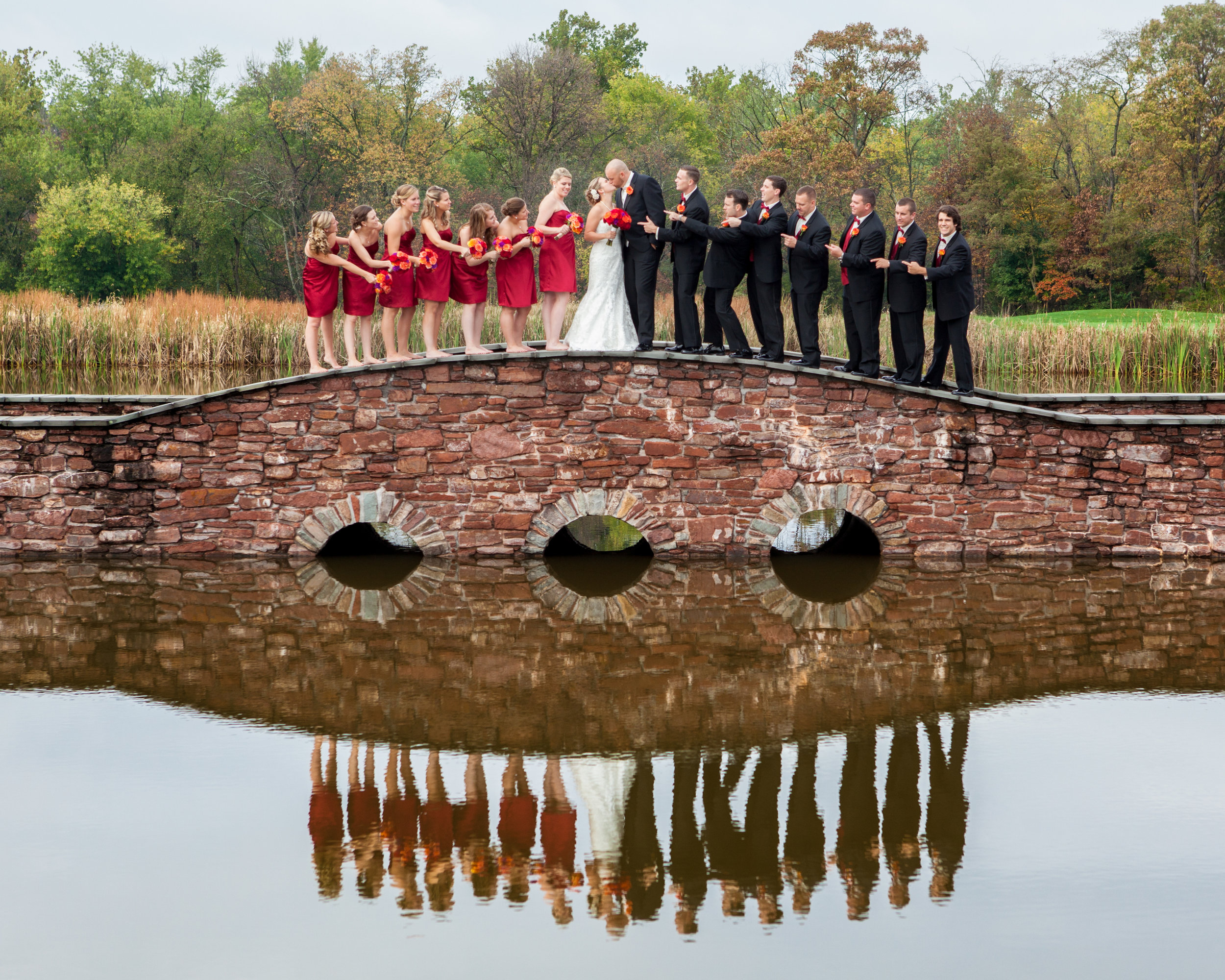 bridal party on bridge bride and groom kissing reflection red orange.jpg