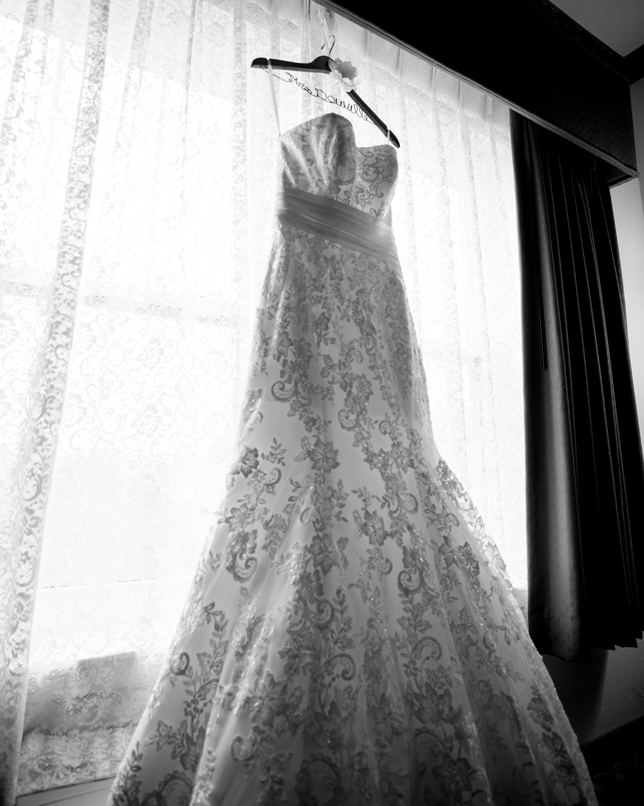 Wedding dress hanging in window before getting ready.jpg