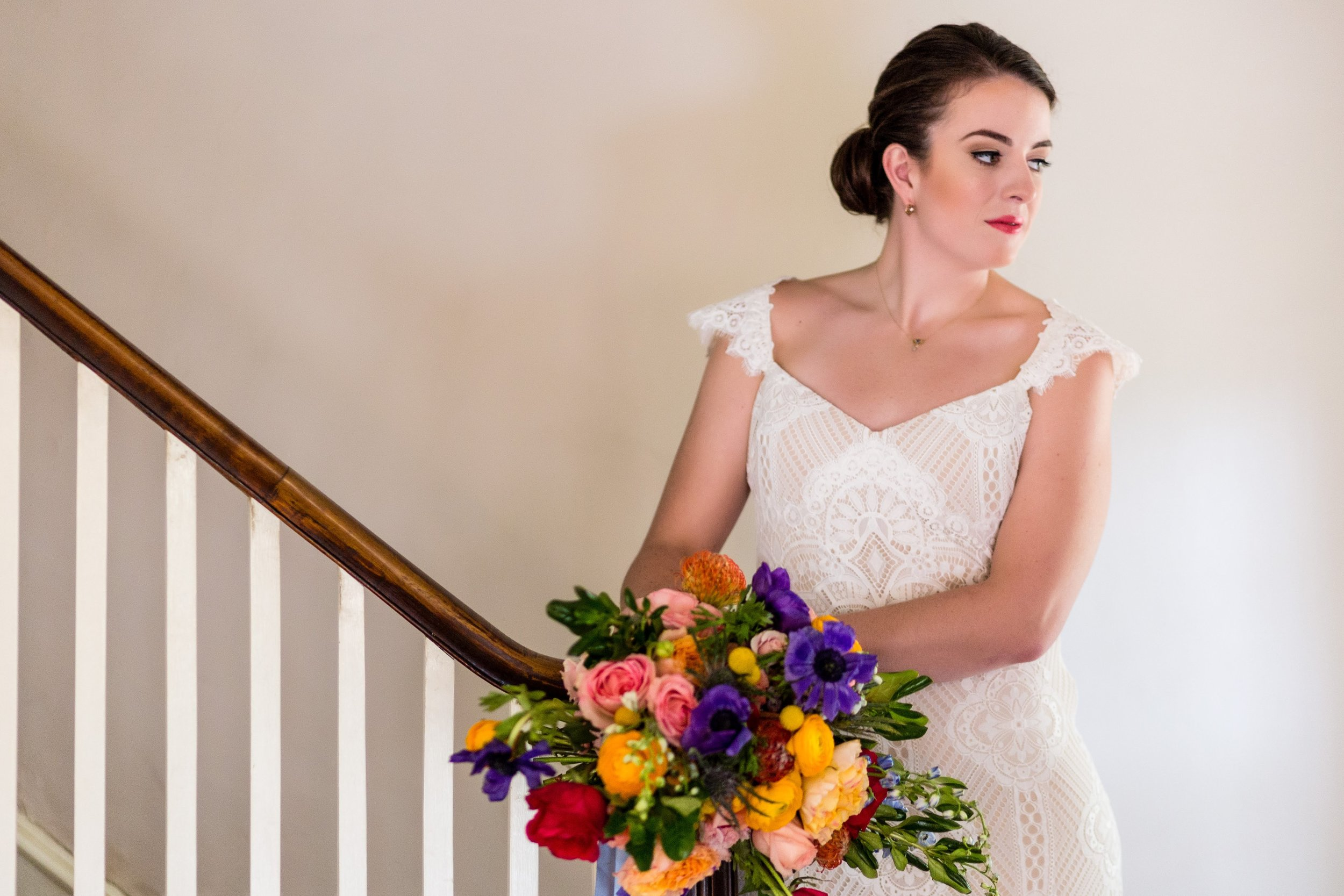 Bride on stairs at Sage Farmhouse colorful bridal bouquet Lavendar Lilacs and Love Ashley Gerrity Photography