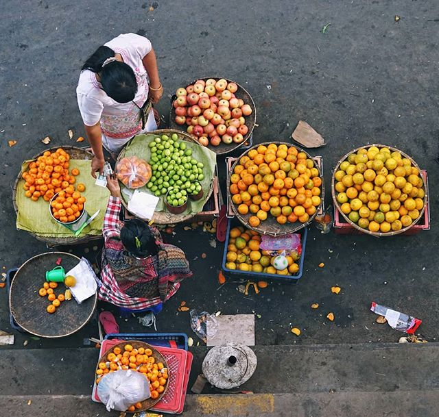 Colours of the Markets  It's a routine.  Early morning, before sunrise, sellers at the street markets head out in the dark to the local fruit and veggie wholesalers.  Digging out their phones, they search for the setting to turn on the flashlight, and shine it on the big piles of produce to inspect it.  If you're going to be selling this stuff to your customers today, you had better have the best  Here in Shan State, much of this stuff comes from nearby, and in some cases direct from the farmers themselves.  The cool mountain air and available water make this the prime location for growing in the country.  That's great for the sellers, and great for the buyers (like you and I!) Too  But getting the best goods is only half of the problem for the street seller.  The next: How do you stand out on a street filled with selling pitching the exact same stuff?  There is a pride in their displays that I often find with street sellers around here. Sometimes, at first glance, you might miss it.  In fact you might just see a pile of stuff, or some lightly organized chaos.  But stick around for a bit and you may just find the method to the madness.  Organizing the goods again between sales, slapping piles of packaged goods with a cloth on a stick to knock away the settling dust from the air, or just sizing up the competition from down the street to make sure they can continue to stand out. It doesn't stop  So when you have a chance, put the camera away and take a minute or two and really watch the action take place.  It's been going on since before you woke up this morning, and chances are they'll still be there long after you've headed away with your basket filled with fresh fruits and veggies too  #UnTourToMyanmar #ThisMyanmarLife #everydayasia #everydaymyanmar #MyMyanmar #visitmyanmar #documentaryphotography #documentary #passionpassport #thediscoverer #atlasobscura #shanstate