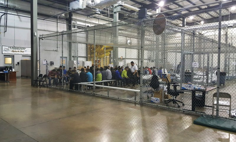 Children are being kept in large cages with chain link walls and concrete floors.