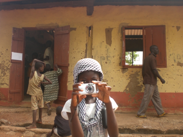 A young Ghanaian girl practices taking photographs at a community exhibition. As part of my PhD research into out of school children's literacy practices, 10 children in two communities in northern Ghanawere invited to participate as photographers. They produced 4,000+ photographs, which are the primary data for my research.