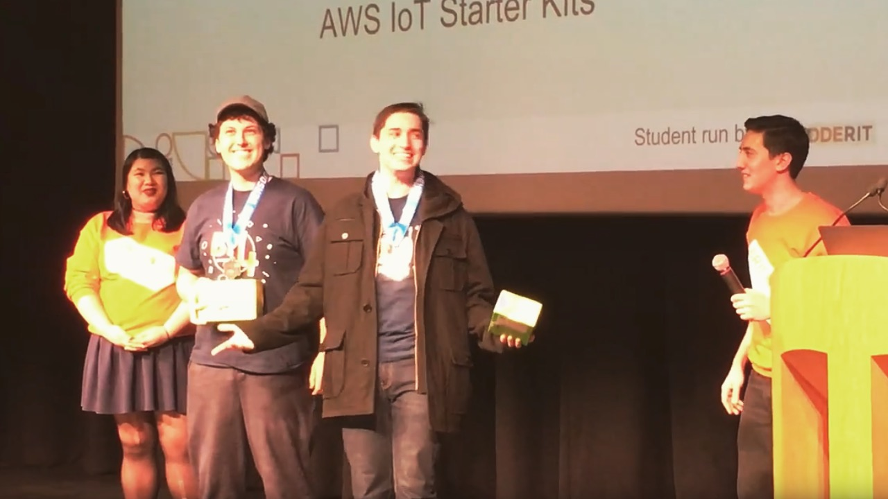 Me (center-left) and teammate, Connor, accepting our IoT award after over 30 hours of no sleep.