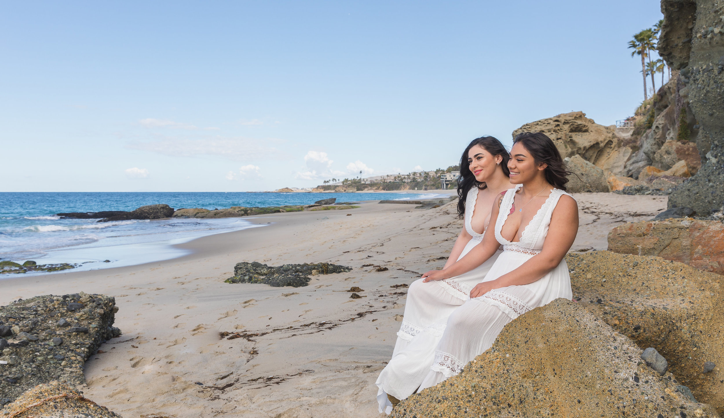 Two Women in White Dress Sitting on the Beach for Engagement Photo Session.jpg