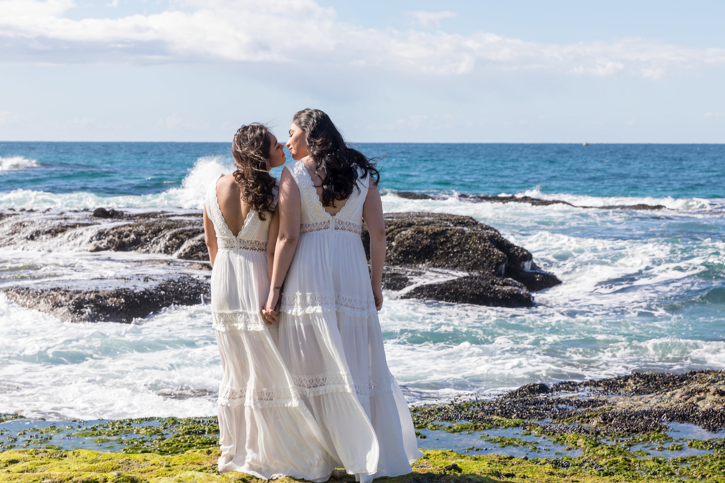 Two women on the beach in long white dresses for engagement kiss.jpg