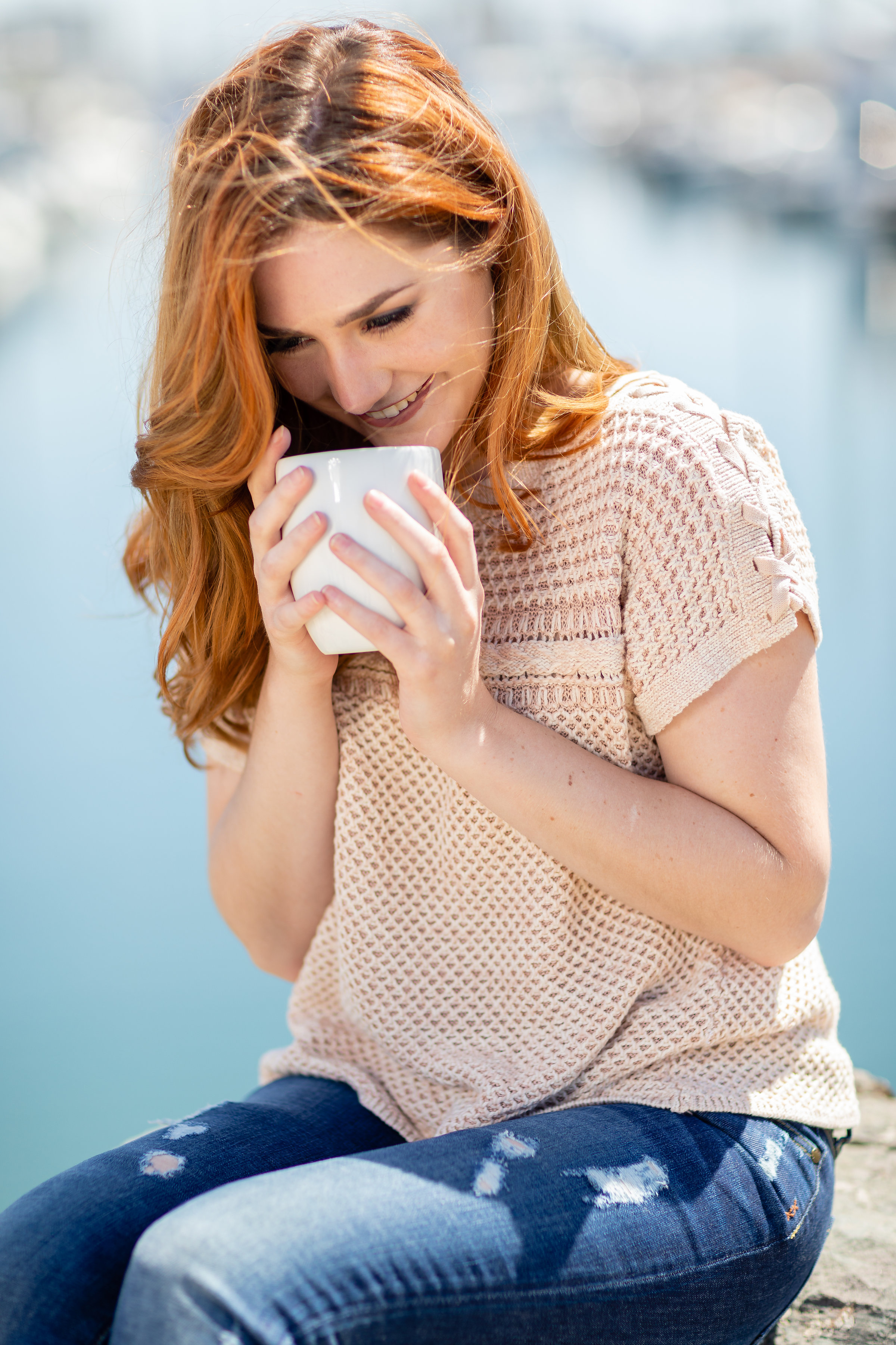 Woman smiling drinking coffee along the water.jpg