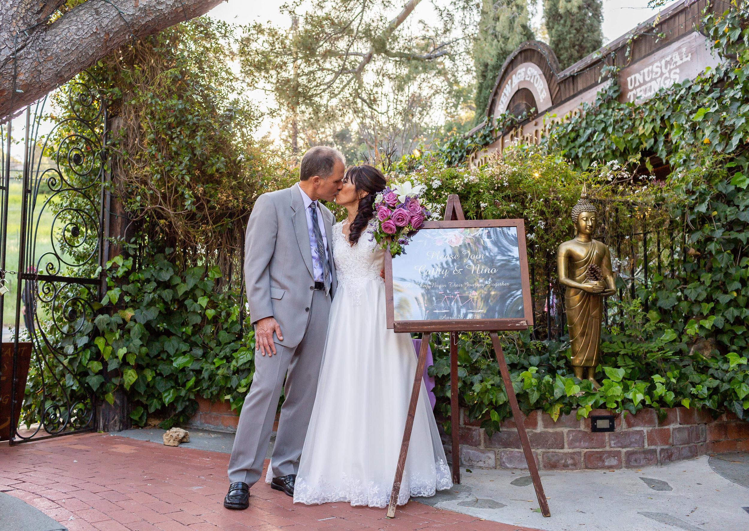 Bride & Groom kissing in front of wedding sign.jpg
