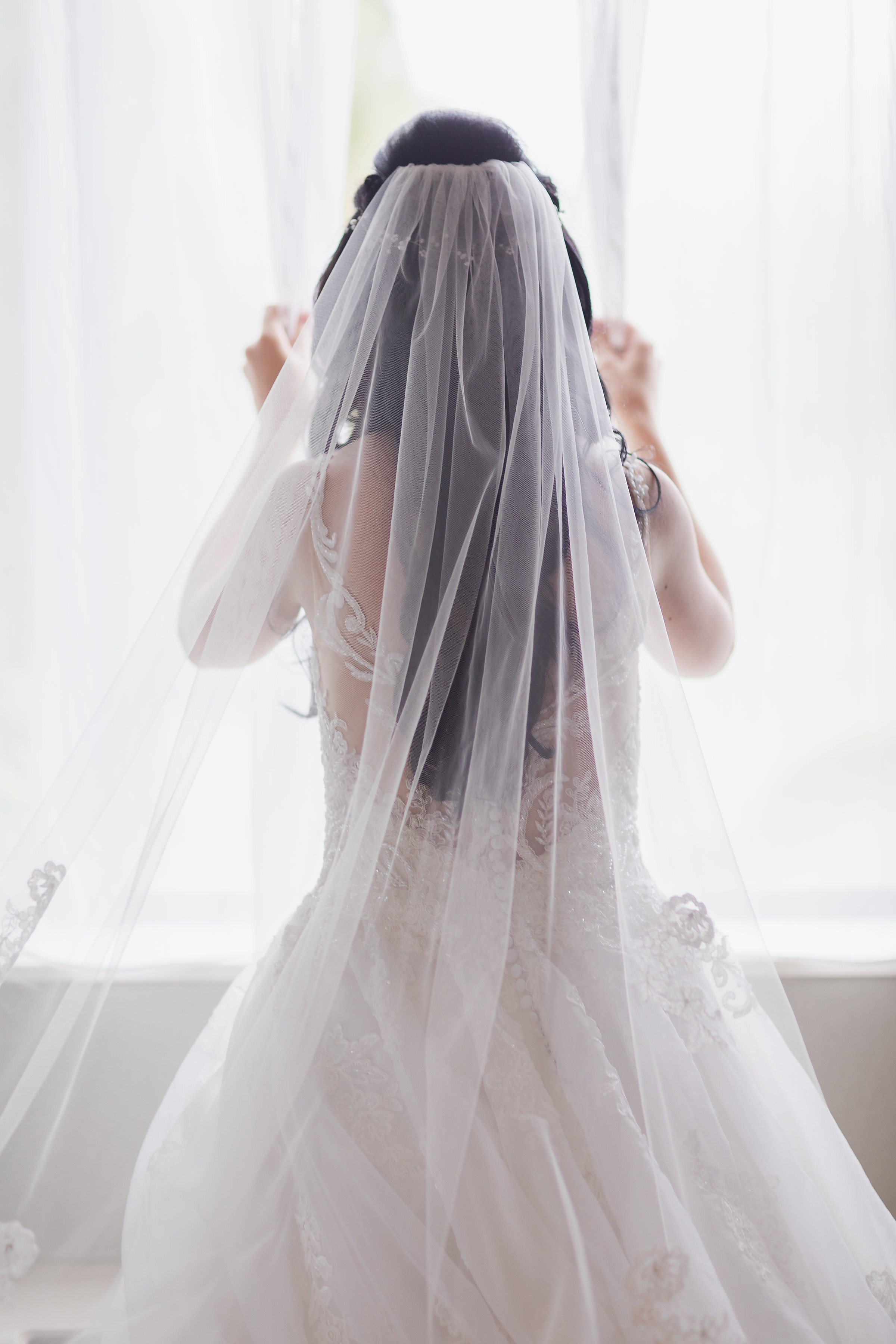 Bride Getting Ready Looking out Window with Veil.jpg
