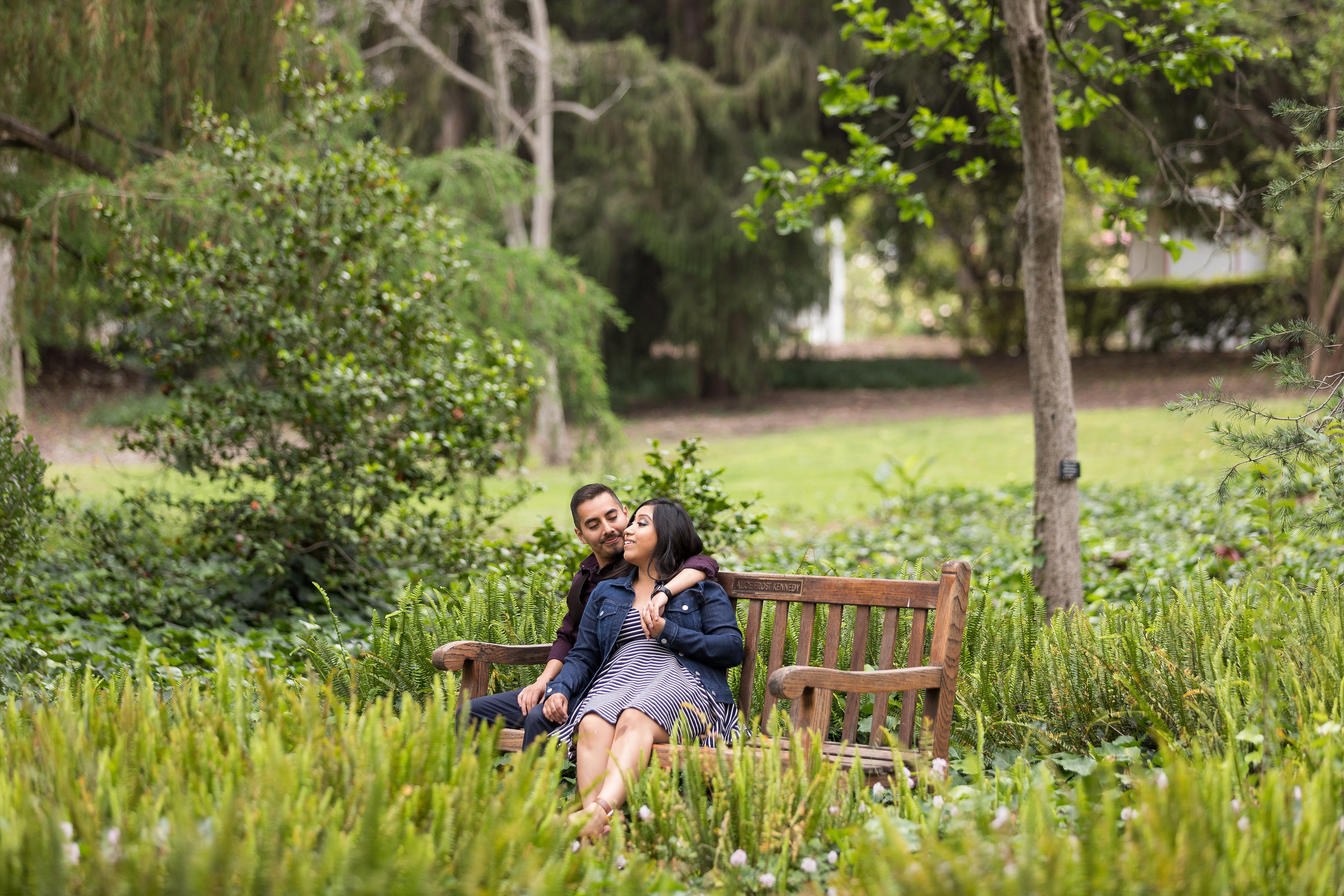 Engaged Couple sitting on a park bench.jpg