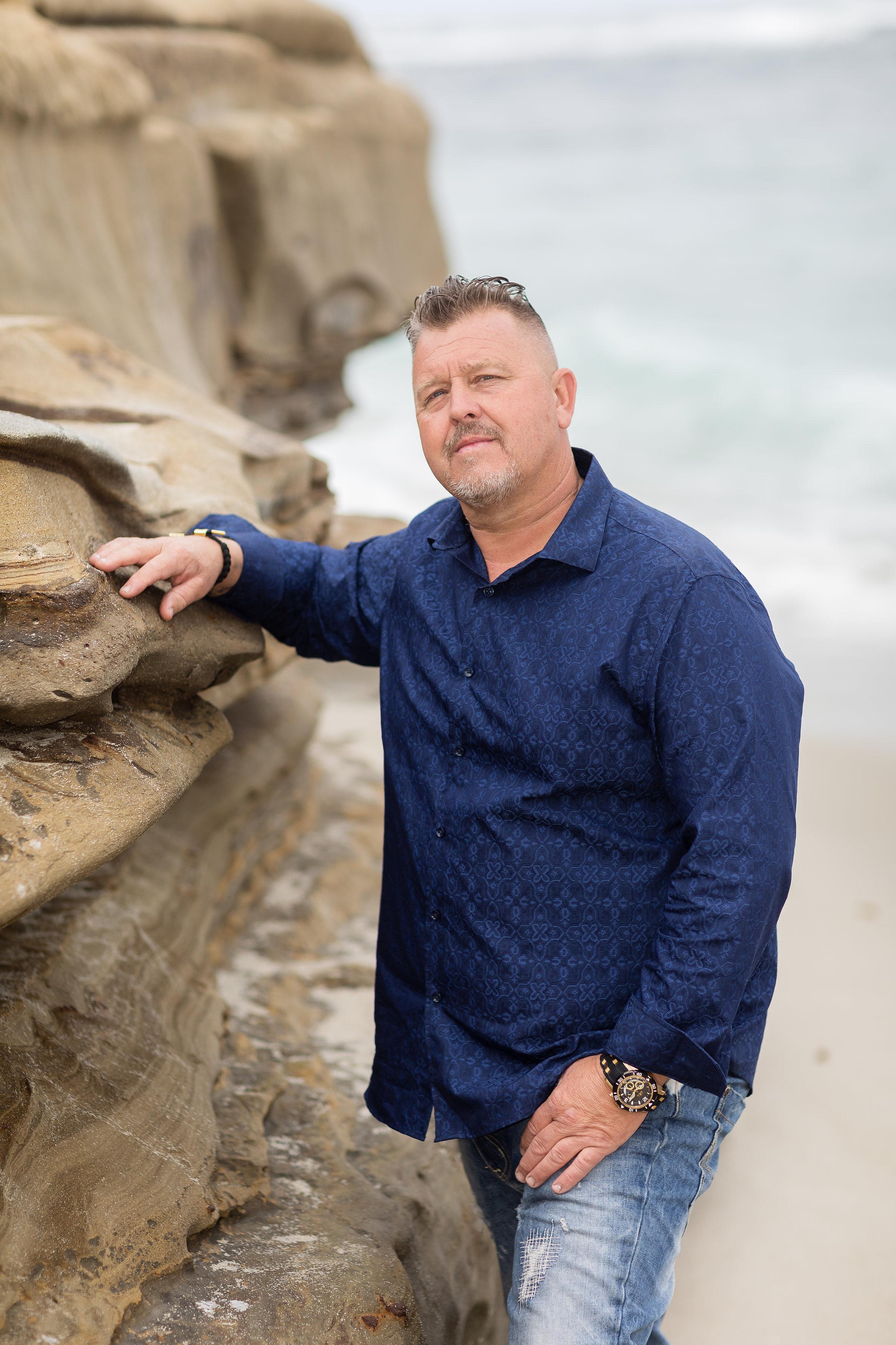 Man in blue short leaning against rocks at beach.jpg