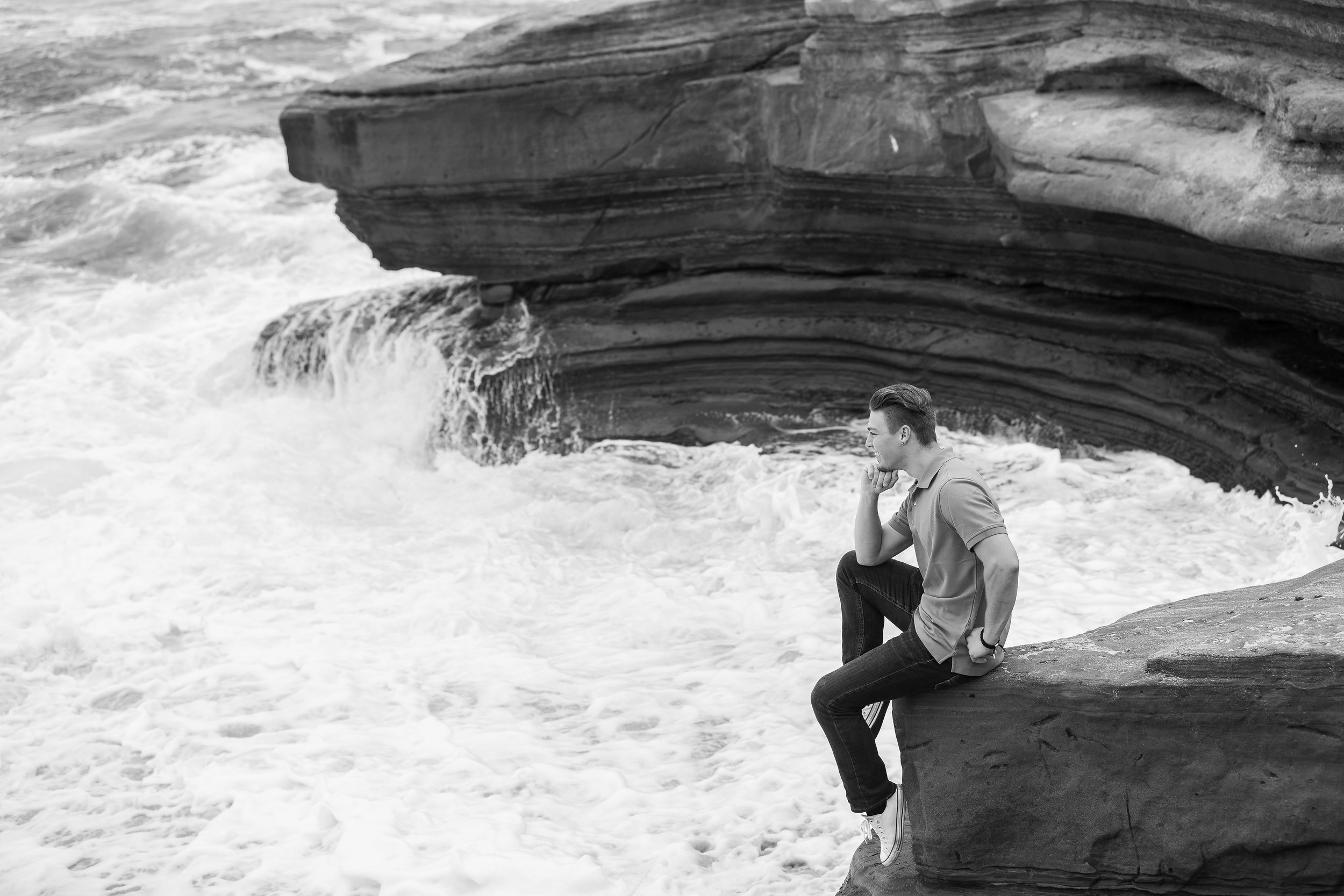 Adult male sitting on rock overlooking ocean thinking.jpg