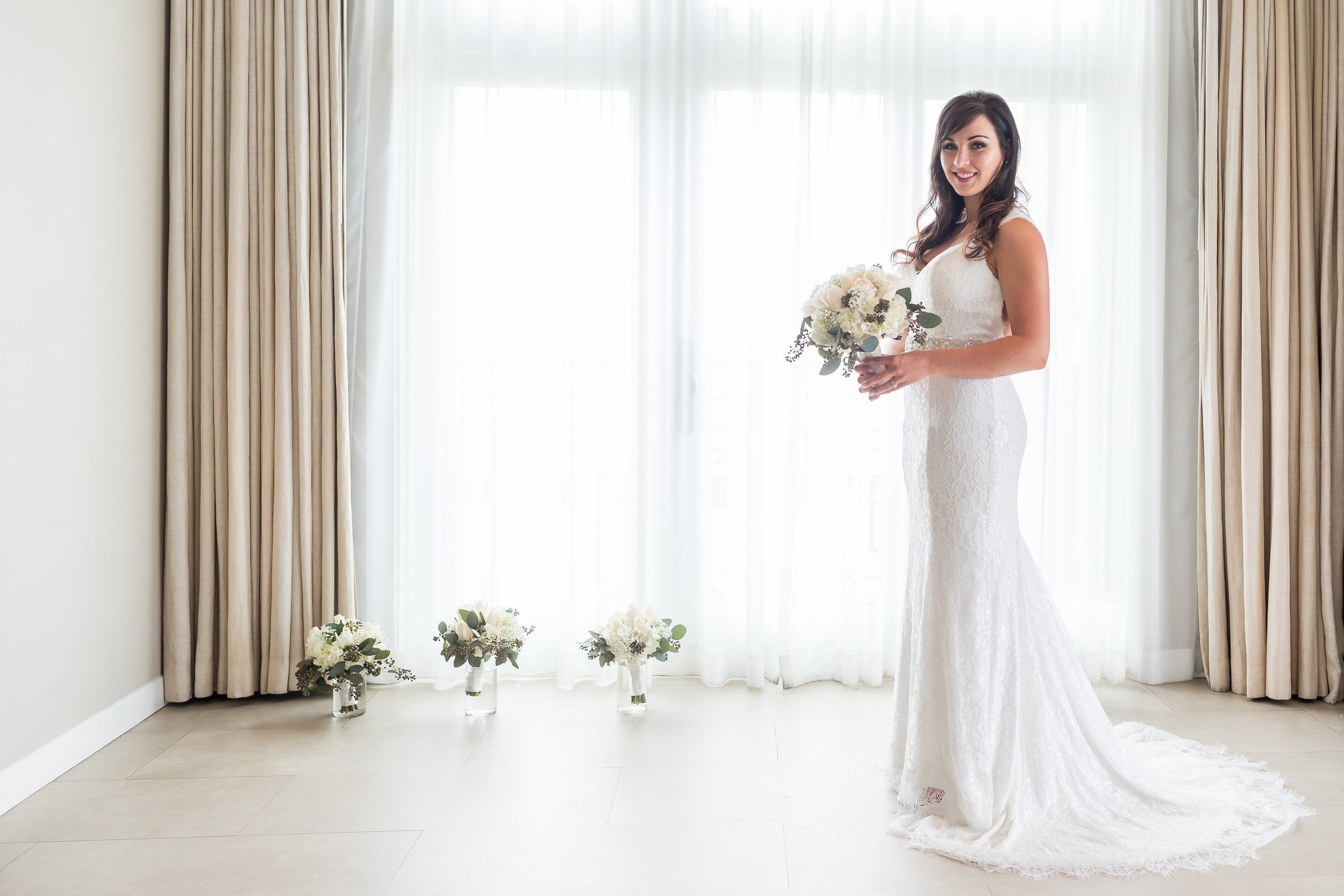 Photo of Beautiful Bride with bouquets in front of tall windows at Hotel Metropole.jpg