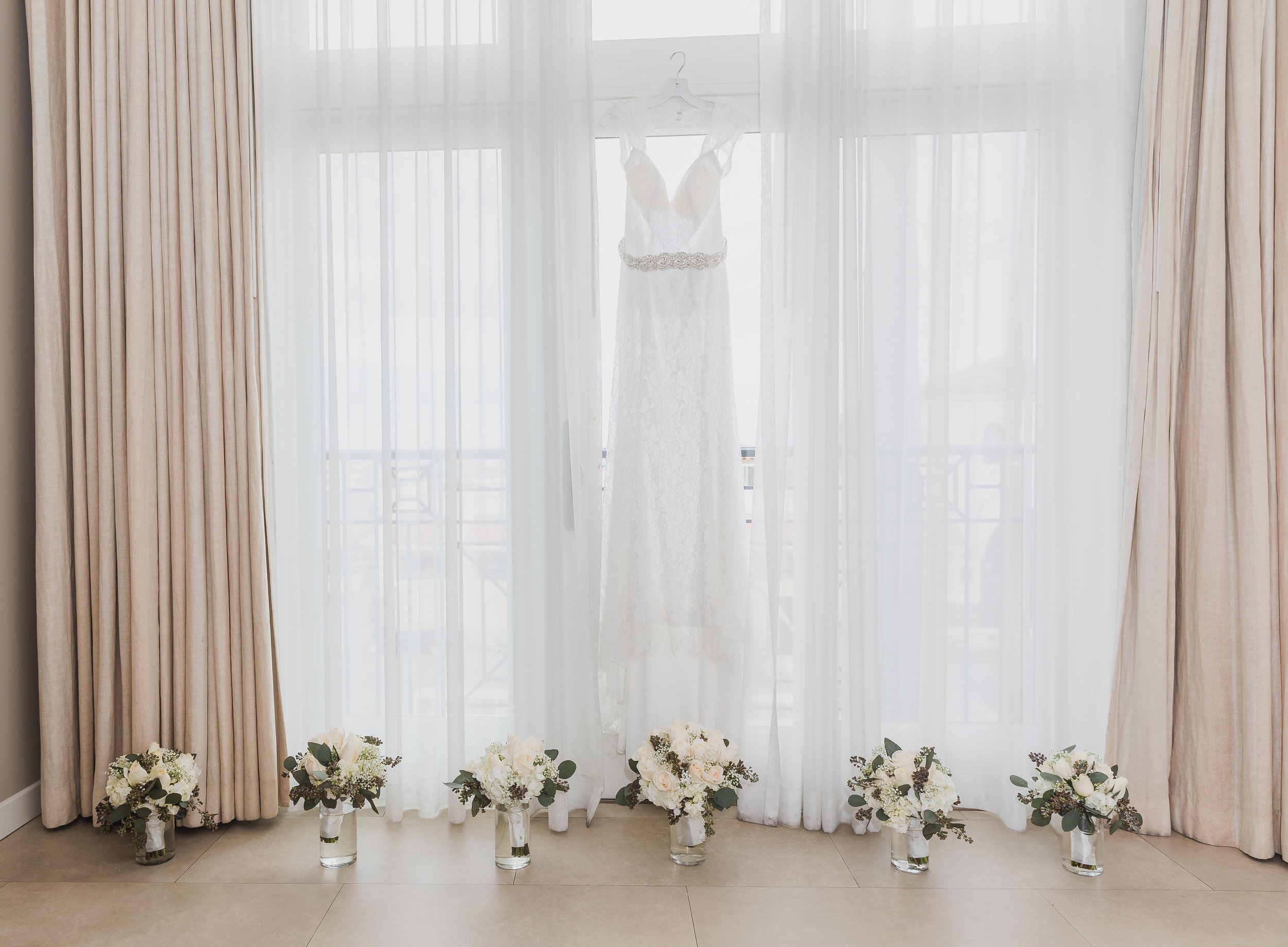 Hanging Wedding Dress surrounded by flowers.jpg