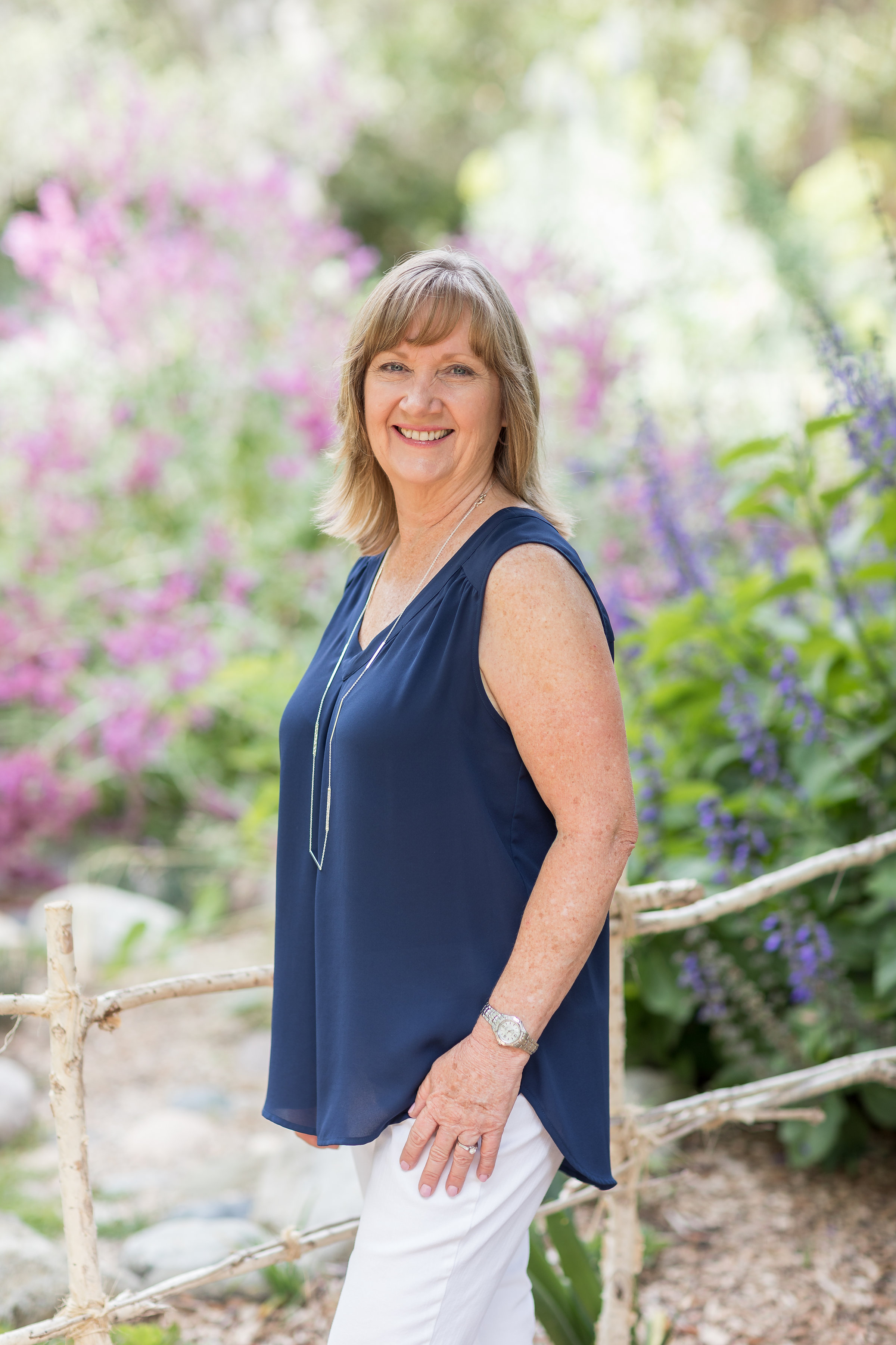 Pretty momma pic in front of an HB garden wearing a blue top and white pants.jpg