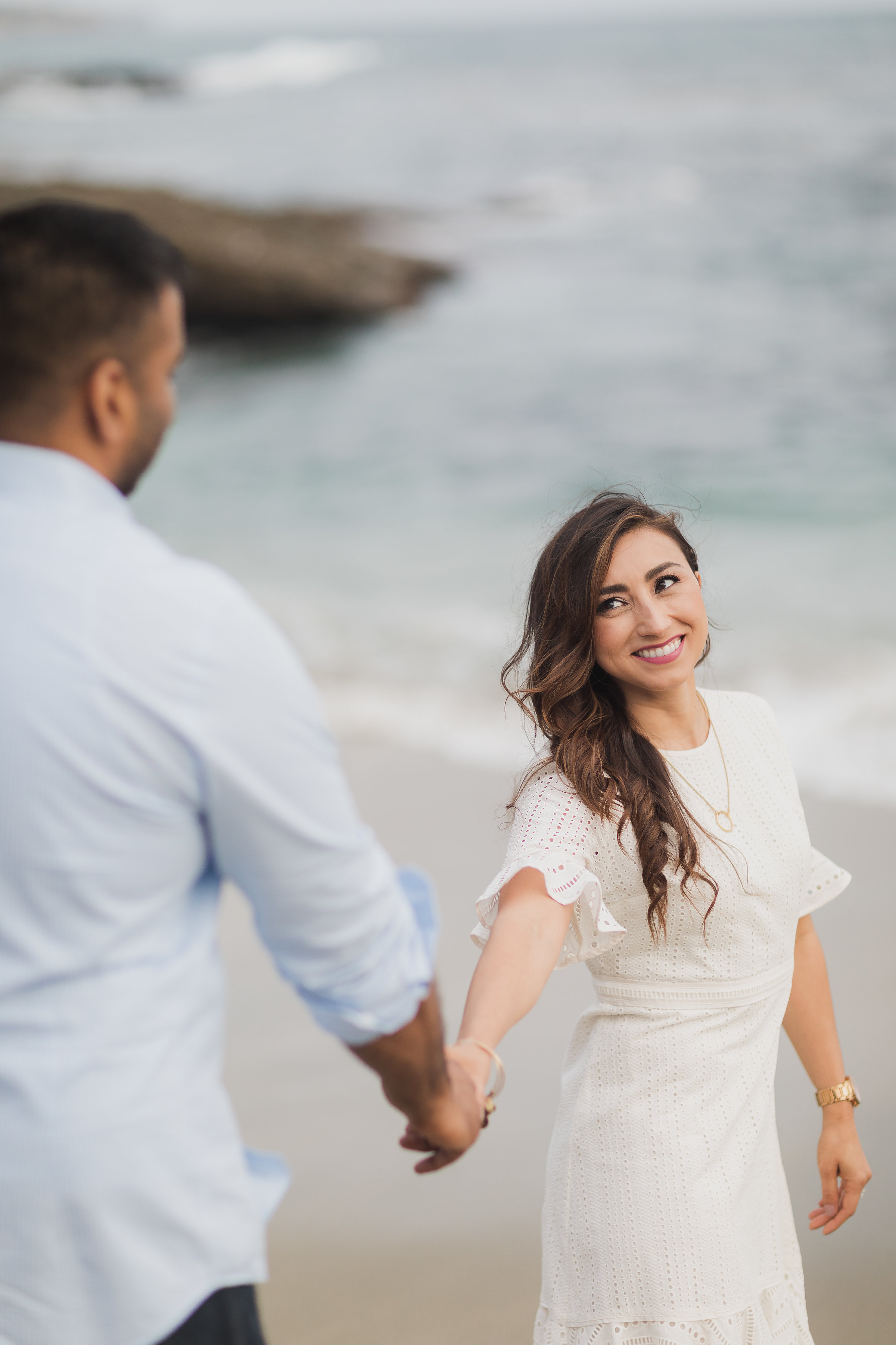 Engagement Photo Session of Girl Leading Boy at the Beach.jpg