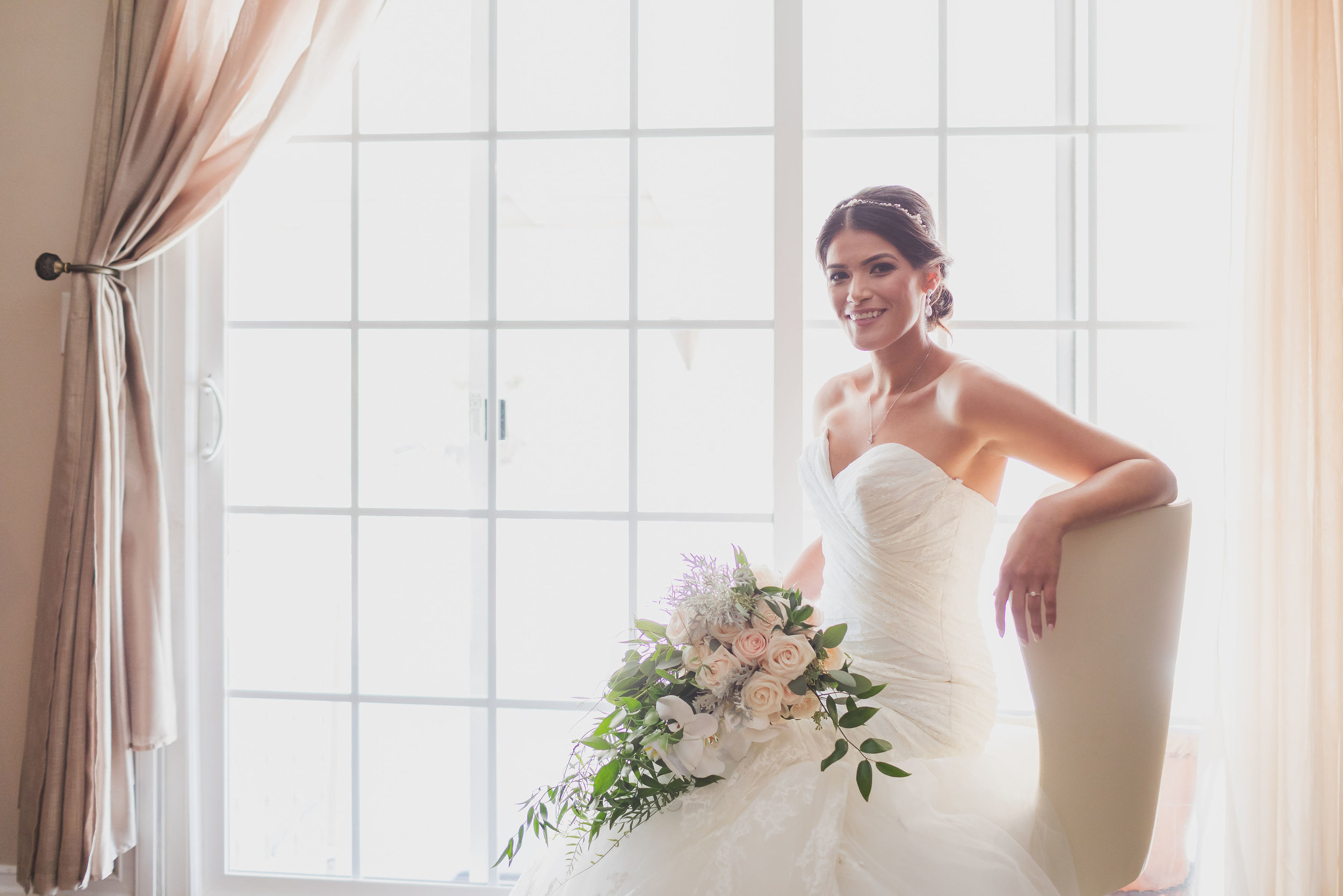 ! Beautiful bride sitting in a chair by the window light with her wedding bouquet.jpg