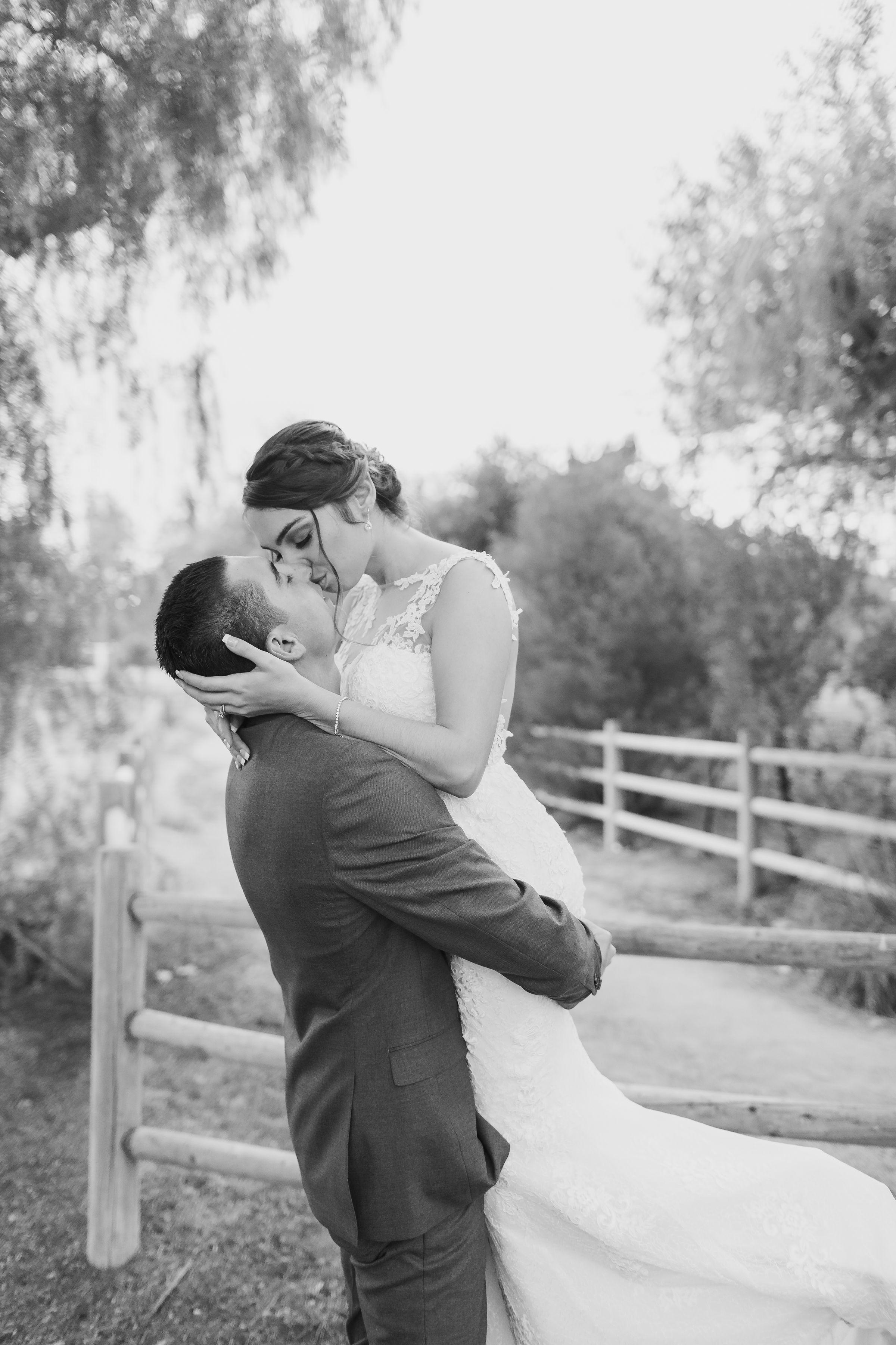 ! Black & White Wedding Portrait Groom Lifts Bride.jpg