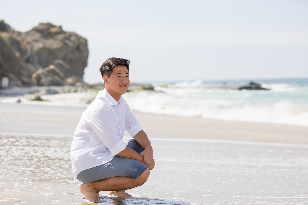 Male senior kneeling in sand at Laguna Beach.jpg